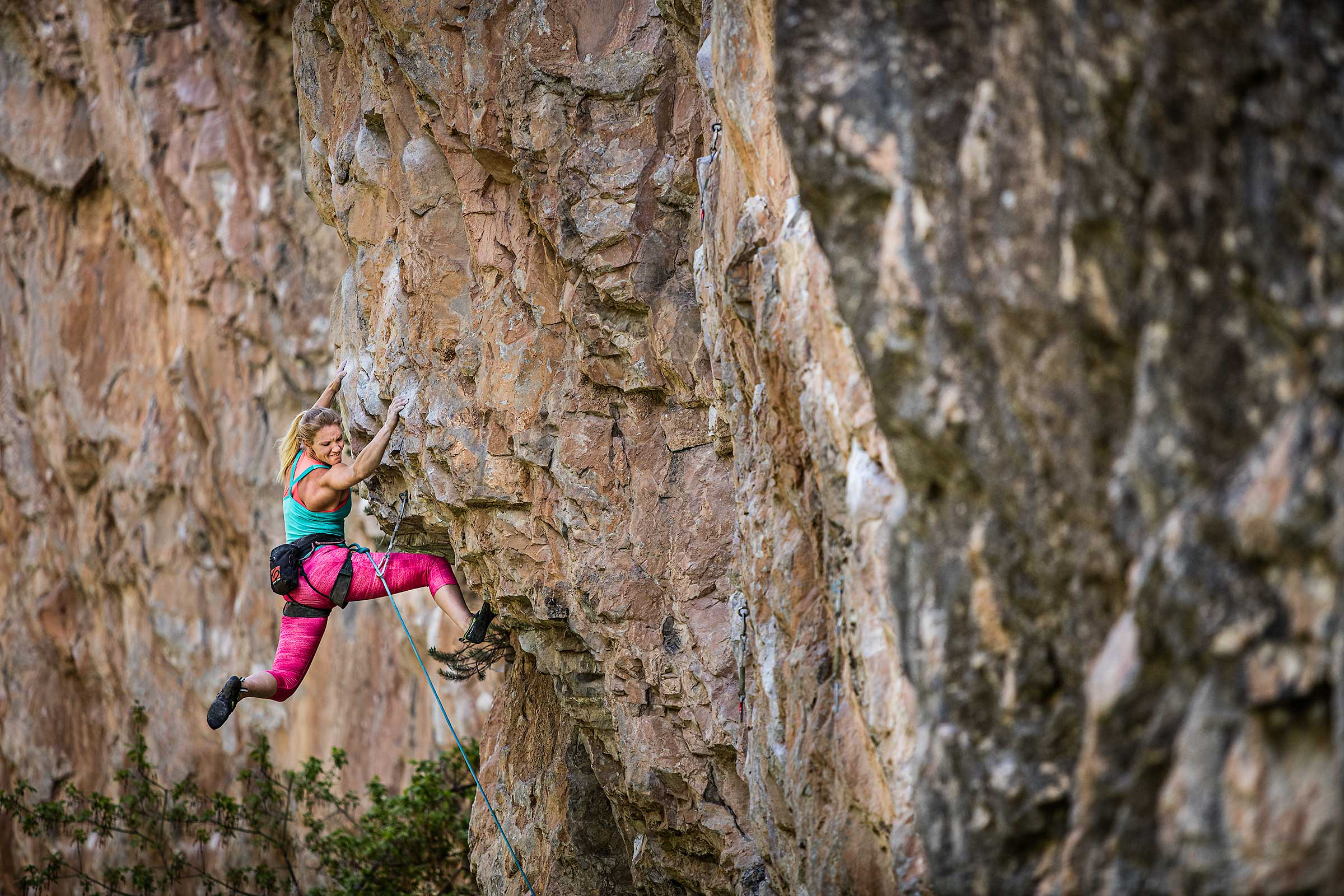 A professional female rock climber swings wildly and struggles to keep from falling