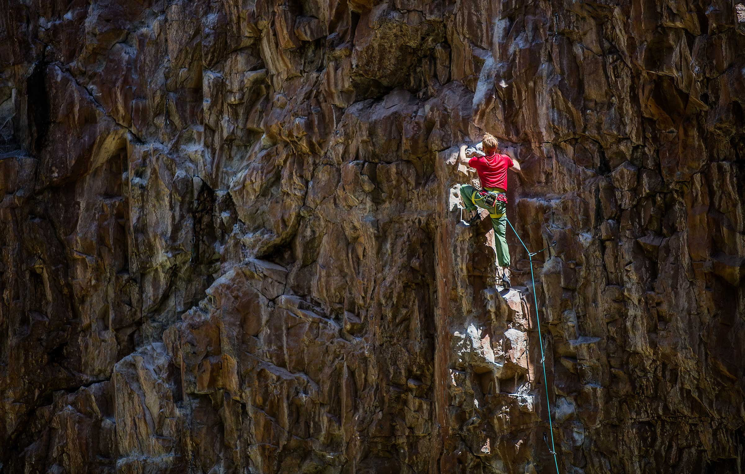 A professional rock climber illuminated by a dramatic shaft of light in Colorado