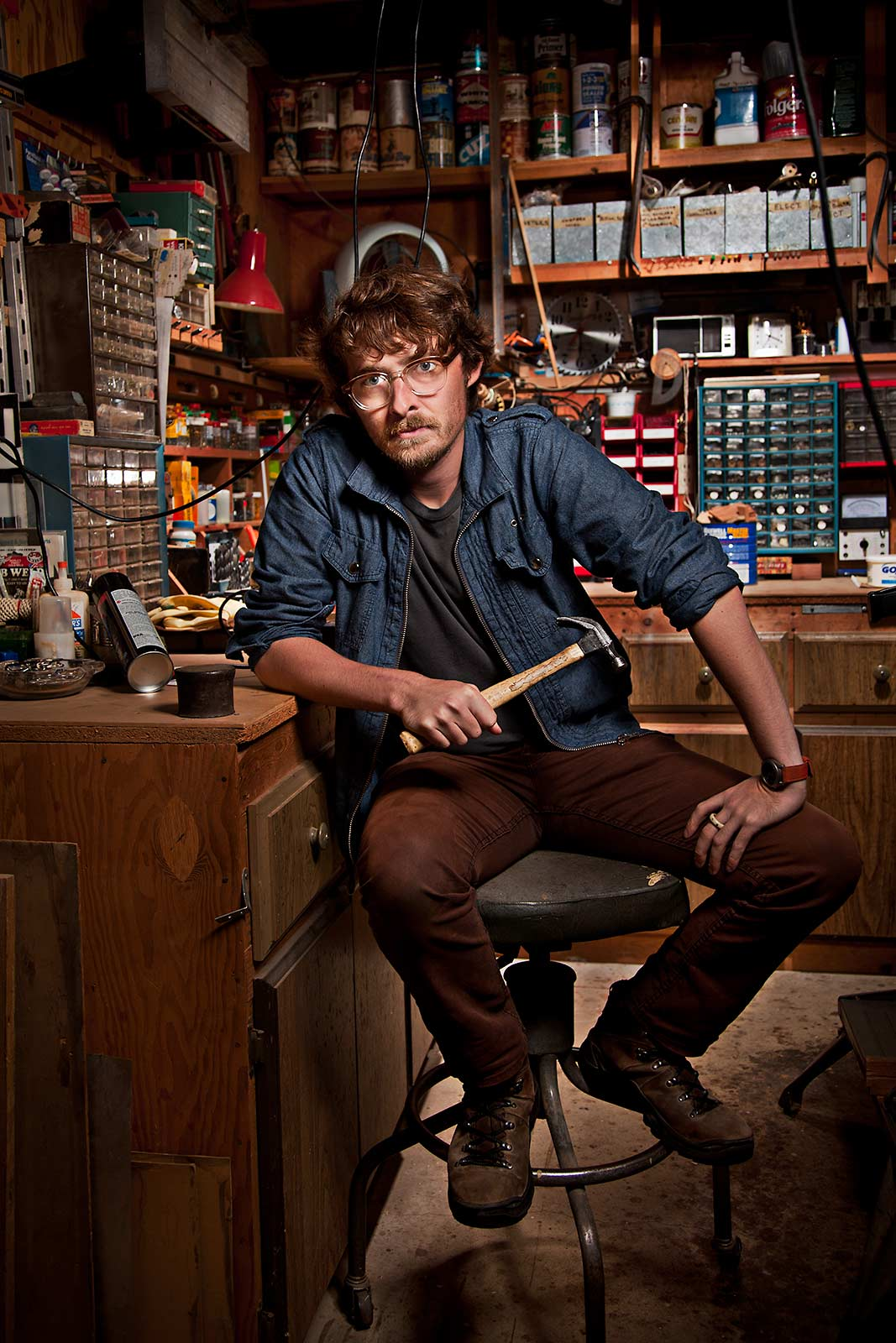 An attractive young hipster poses in his woodworking workshop in Brooklyn NY
