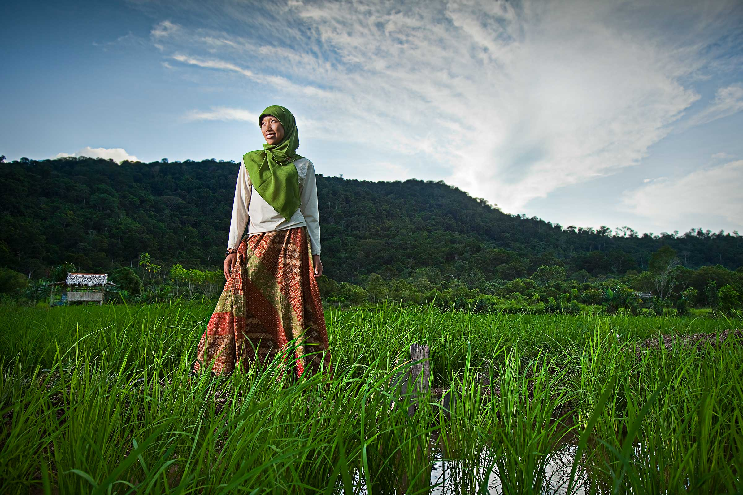 a woman in beautiful traditional muslim clothing poses among rice paddies in Kalimantan Indonesia