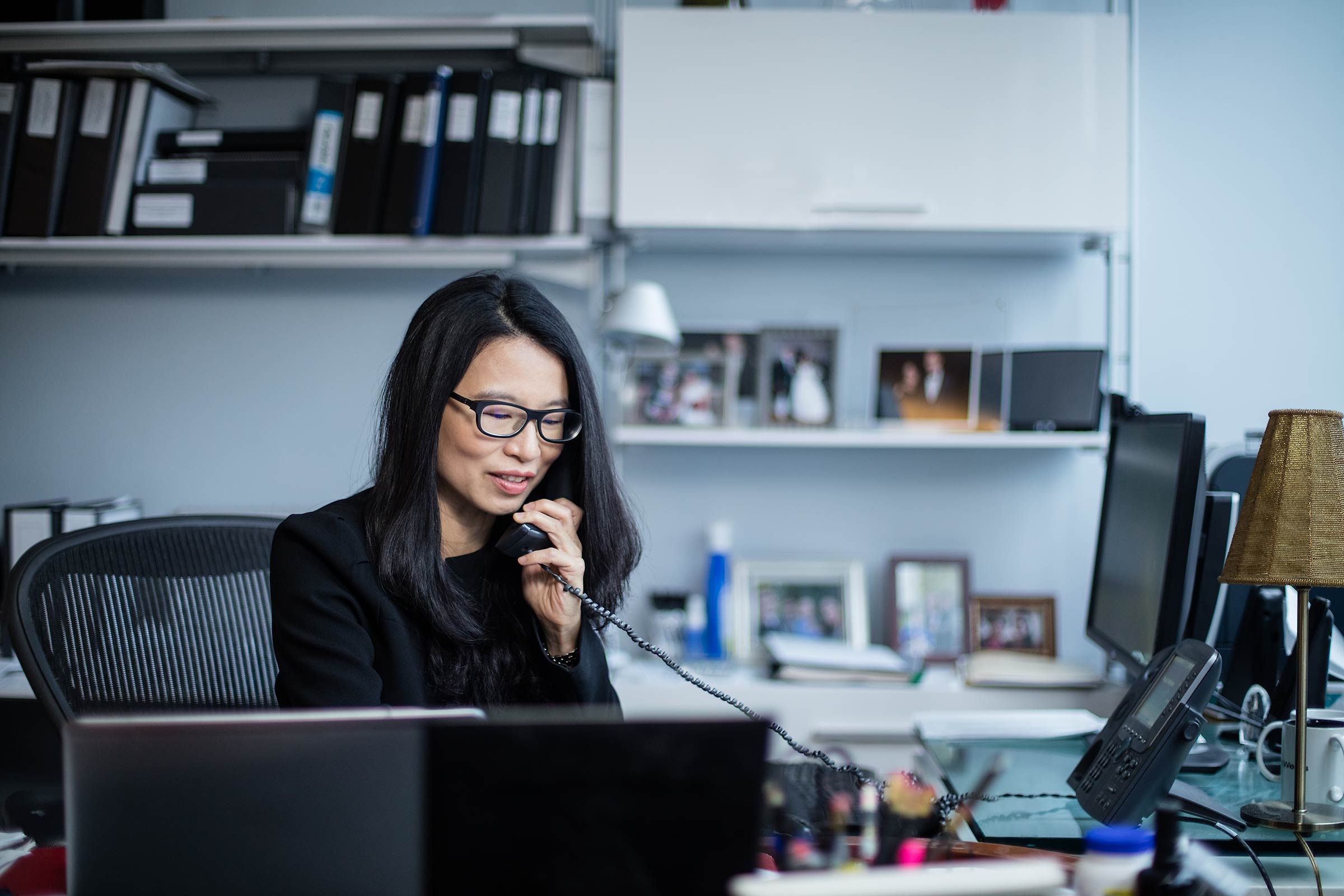 An Asian woman executive on the phone in her New York City Office