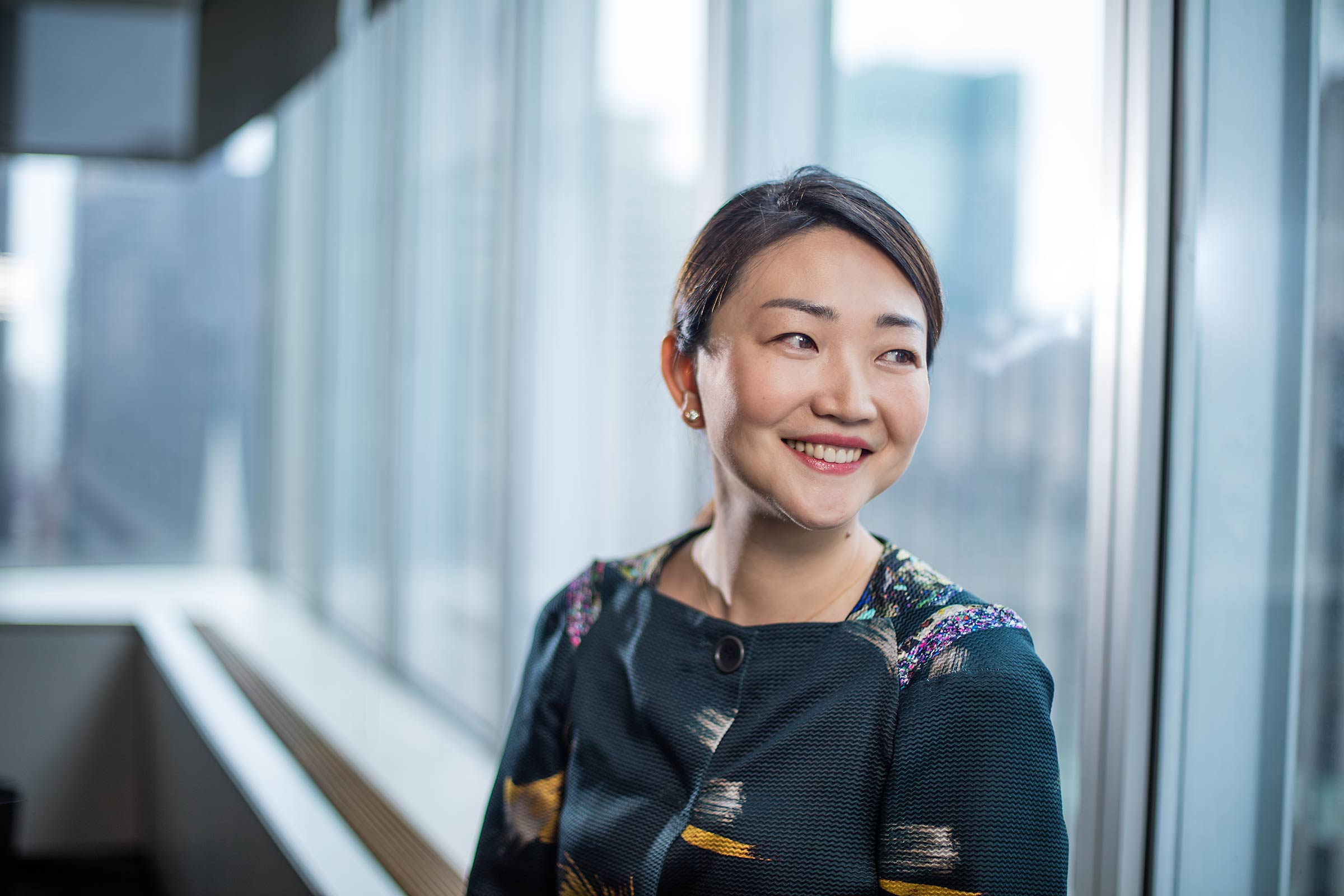 A female Asian executive smiles out the window of aNew York City office