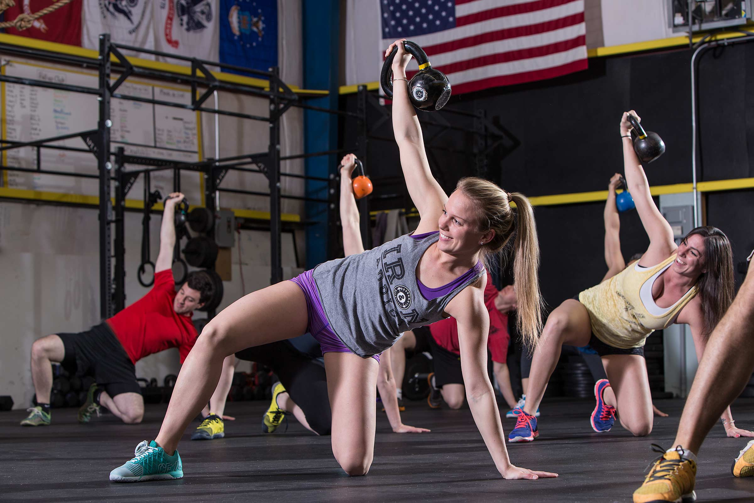 A young woman smiling while engaged in a group Crossfit Workout