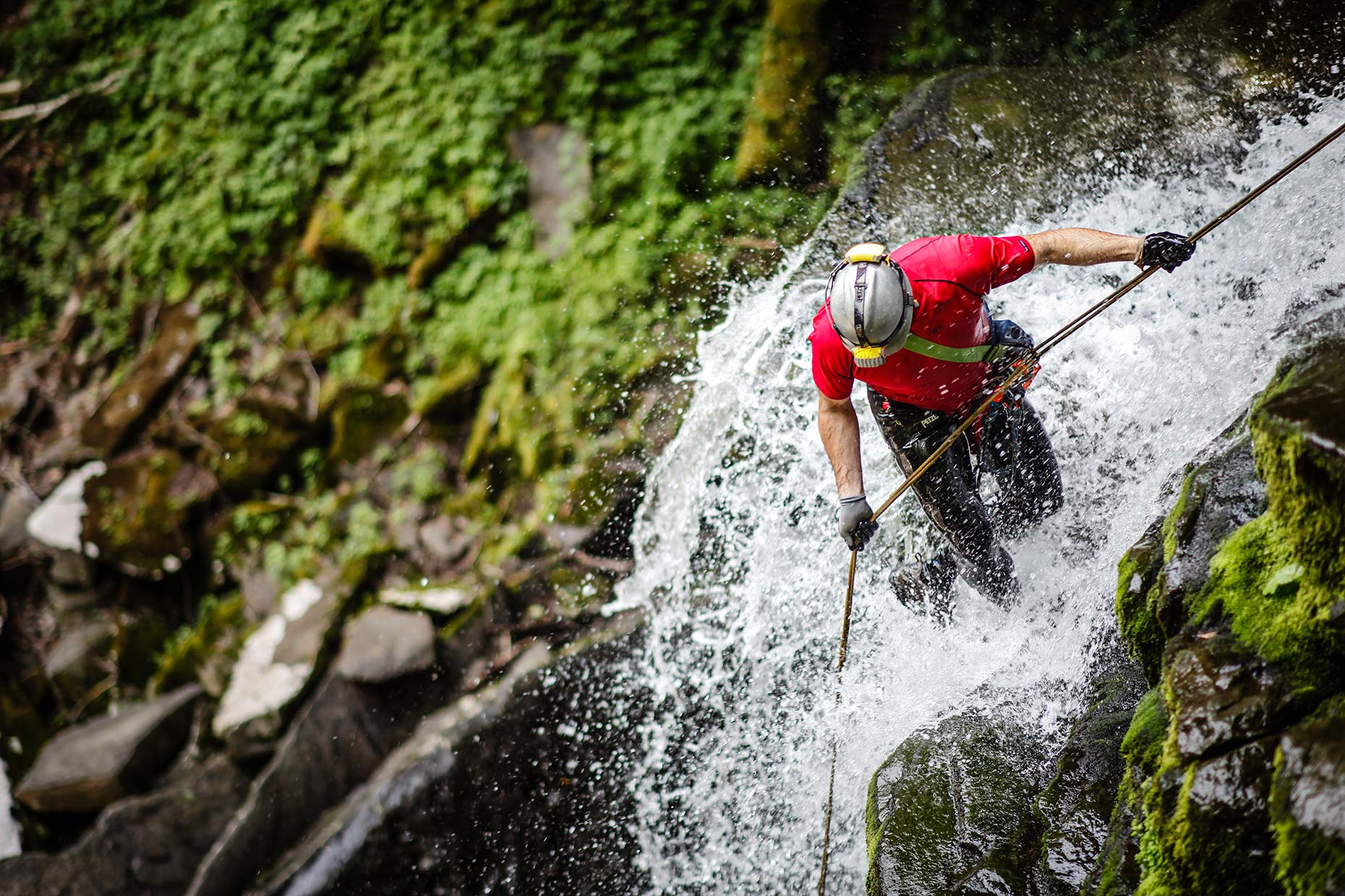 A canyoneer rappels down a powerful raging waterfall in the Catskills New York