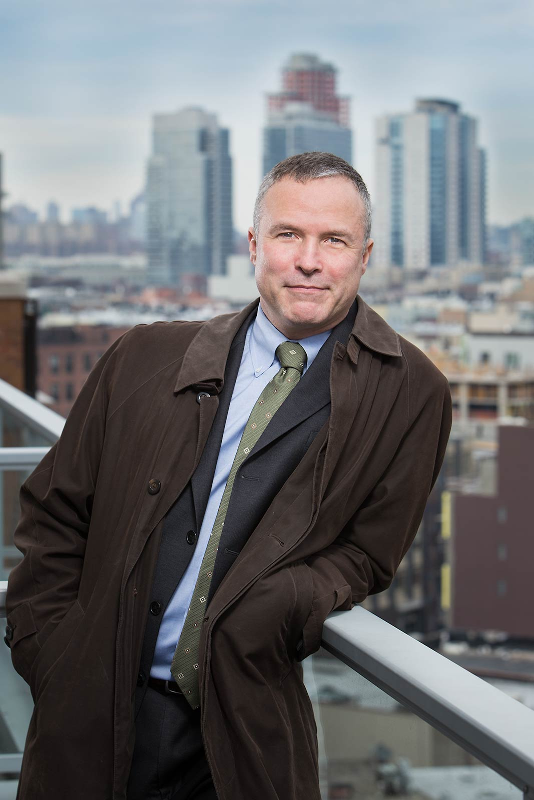 Casual outdoor portrait of doctor on balcony with New York skyline in background
