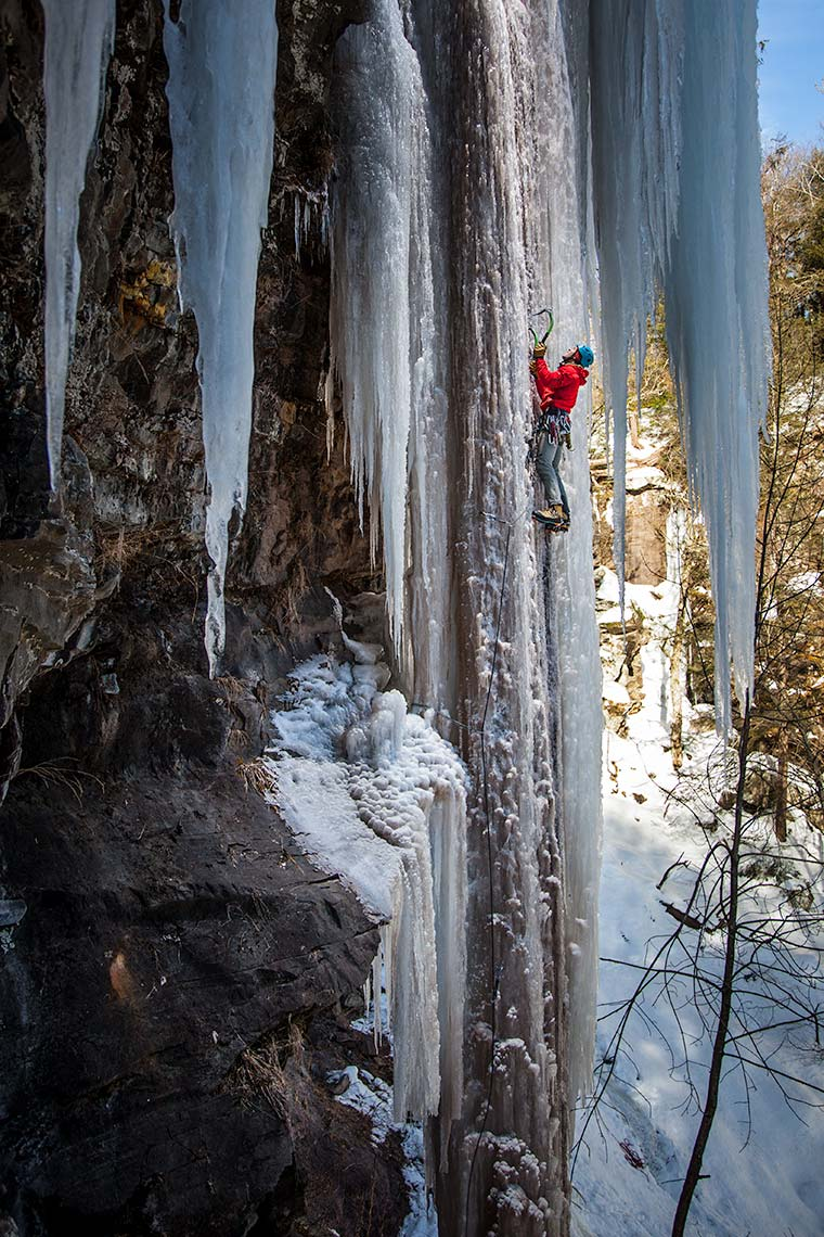 an ice climber ascends a dramatic icicle hanging from a Catskills cliff in New York