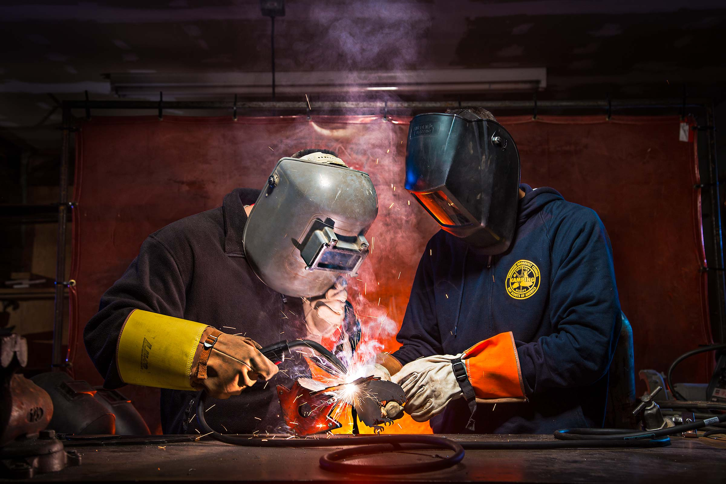 Two Young men learning to weld steel at a Boyscouts of America Camp