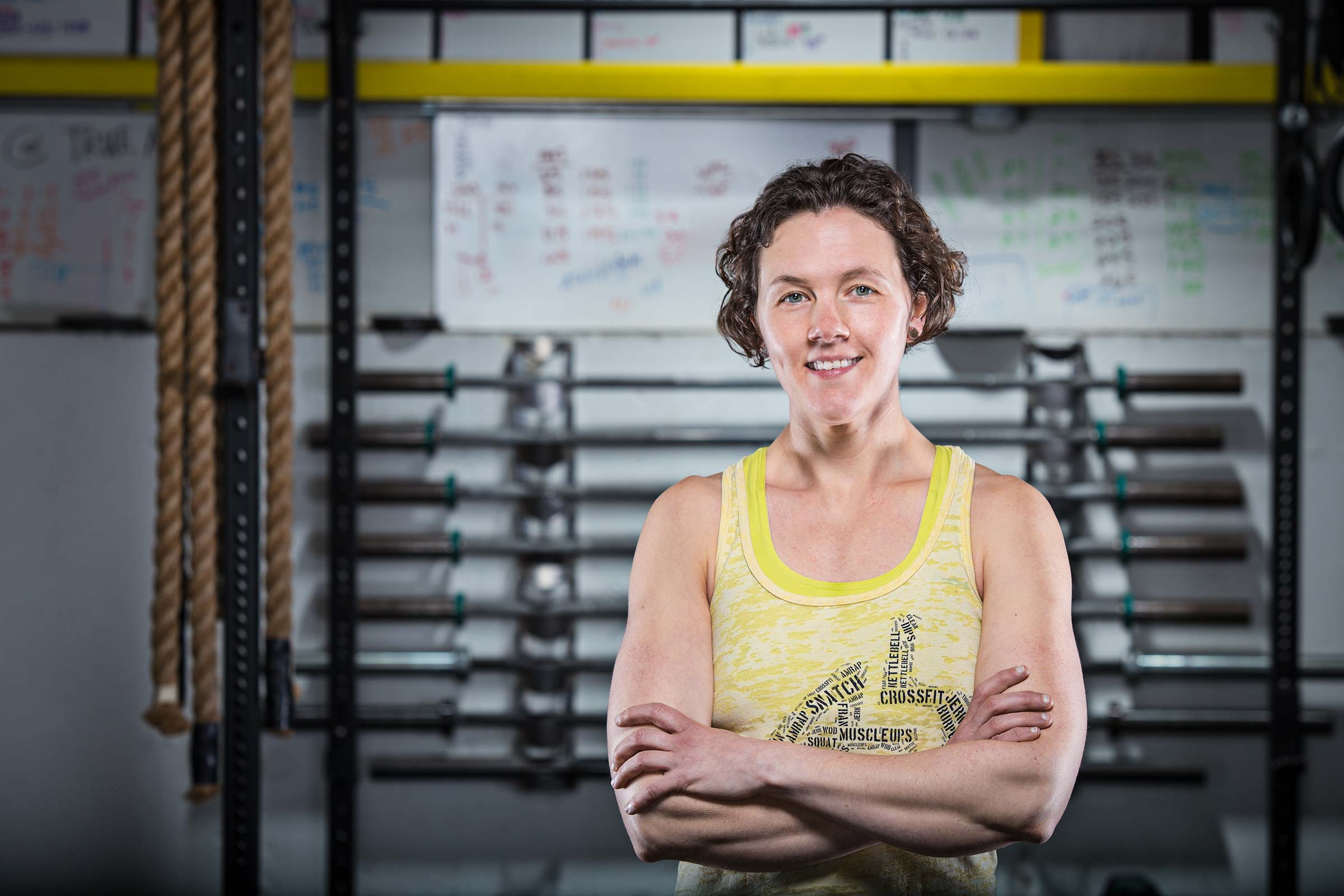Upbeat portrait of a female crossfit trainer in front of equipment in Connecticut gym