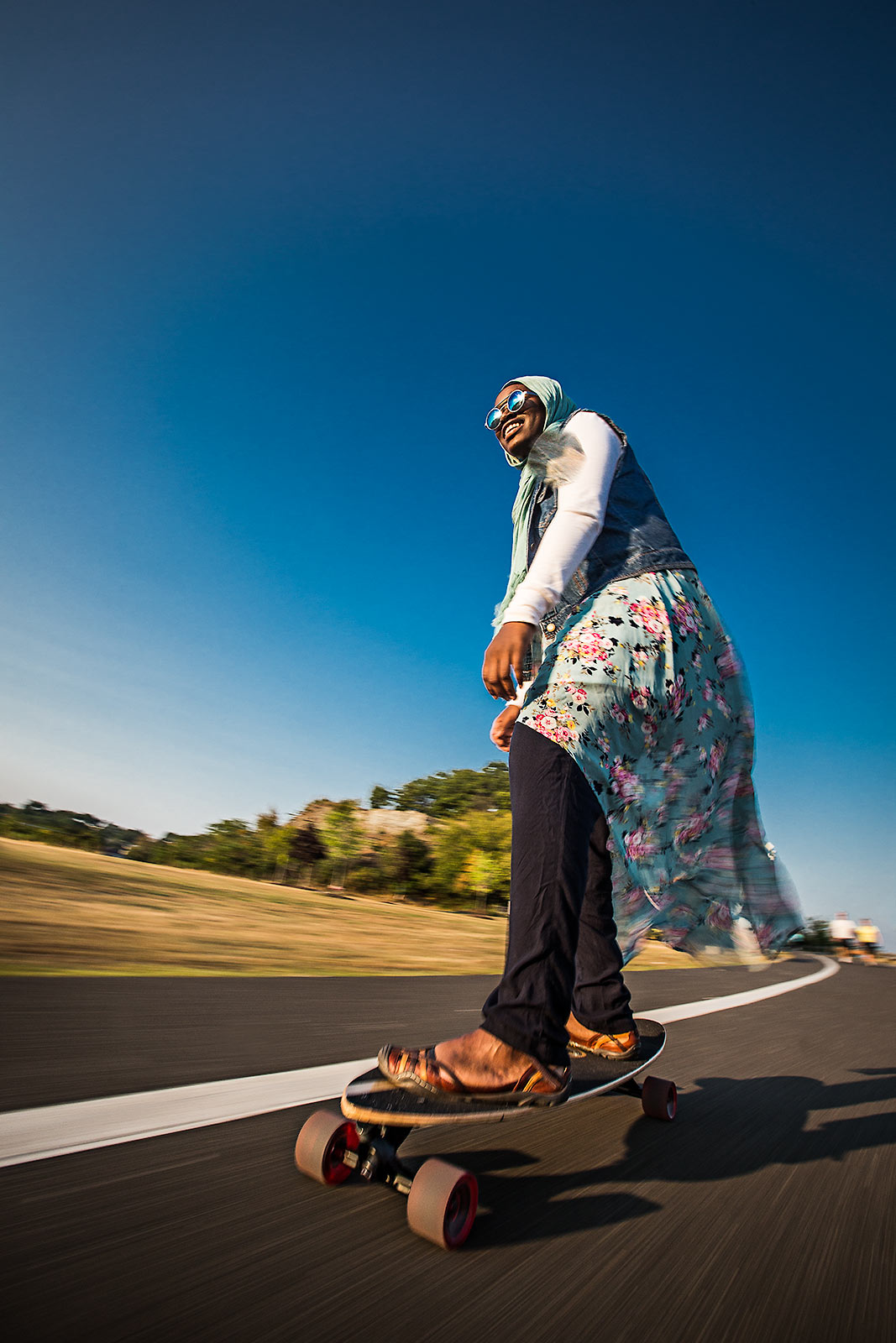A young muslim woman wearigna headscarf riding a skatebaord at a Connecticut beach