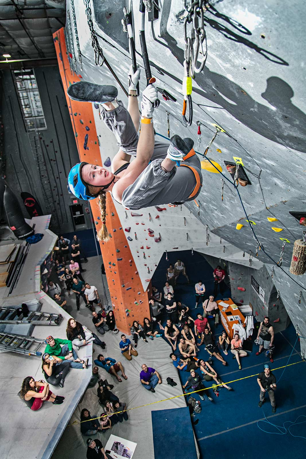 A young professional female ice climber competing in an indoor ice climbing contest