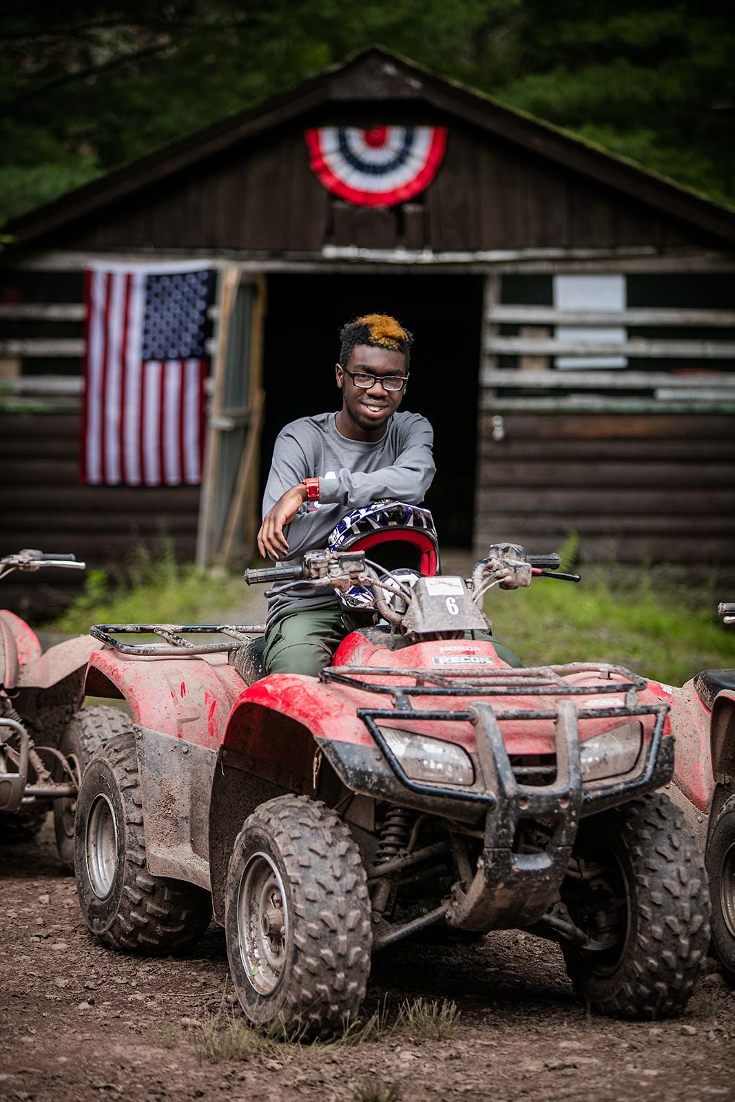 Portrait of smiling African american male teenager on ATV at Camp in New York