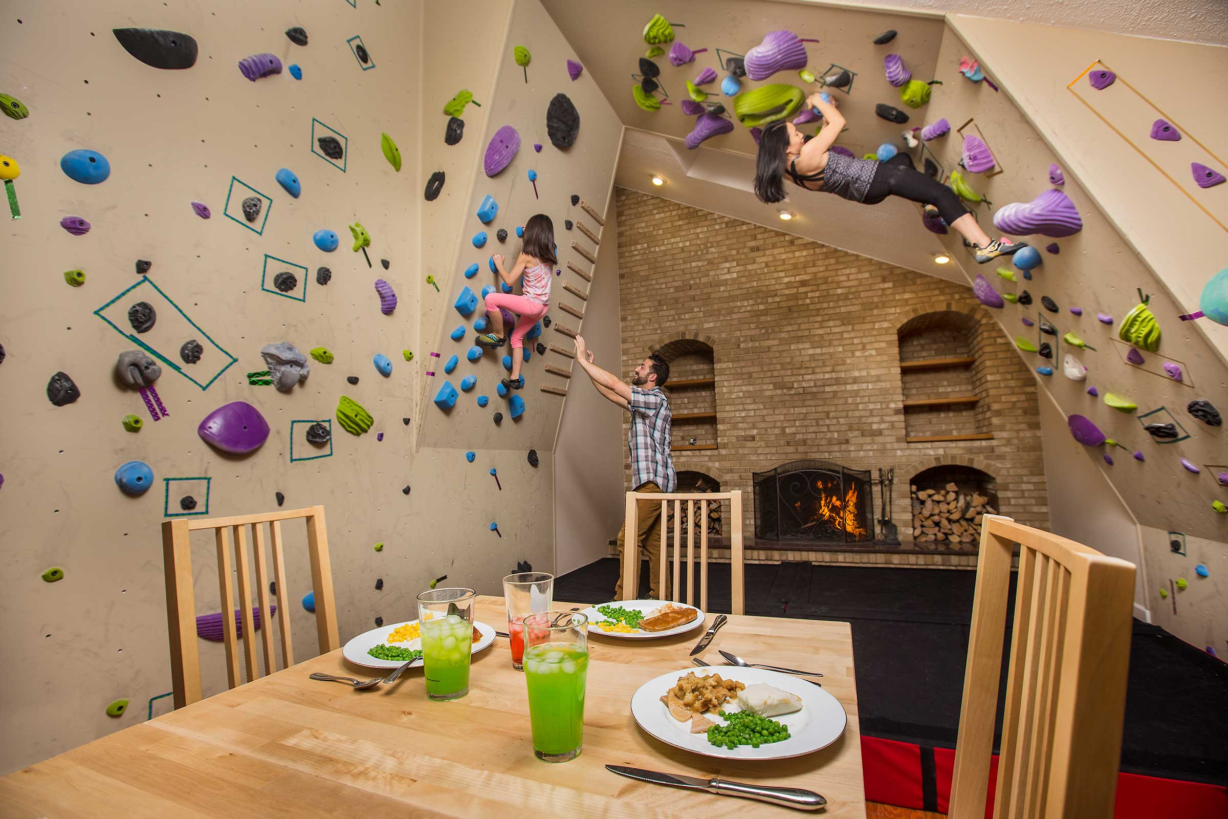 A multiracial family rock climbing in their living room