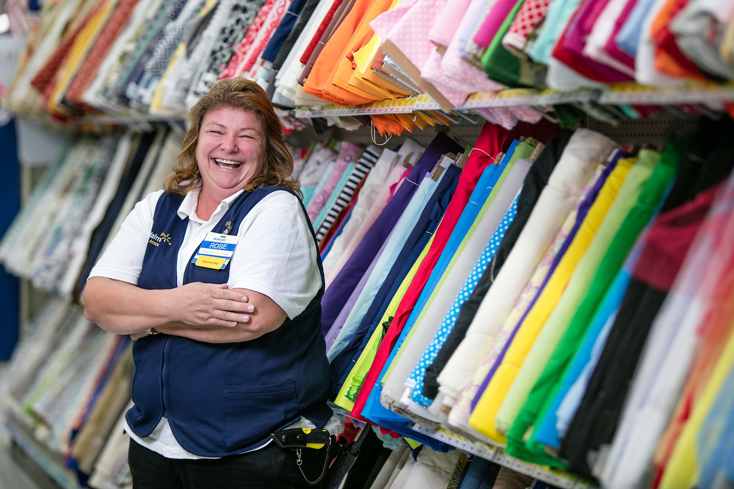 A retail employee laughing in a store aisle while at work