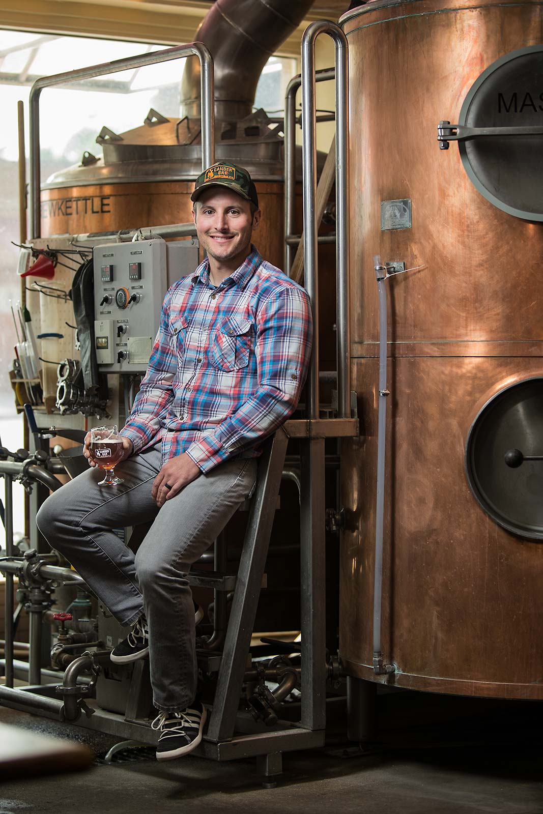 A brewmaster and resturant owner smiles next to his brewing facility Lander Wyoming