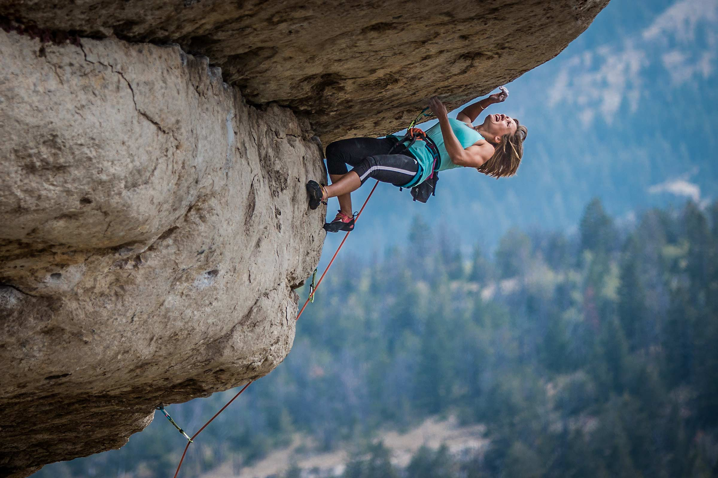 A muscular female rock climber pulls over a difficult horizontal roof in Wyoming