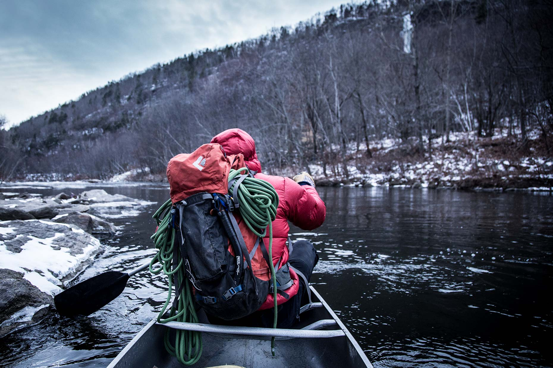 An ice climber in a canoe with climbing pack and rope paddles a river in winter