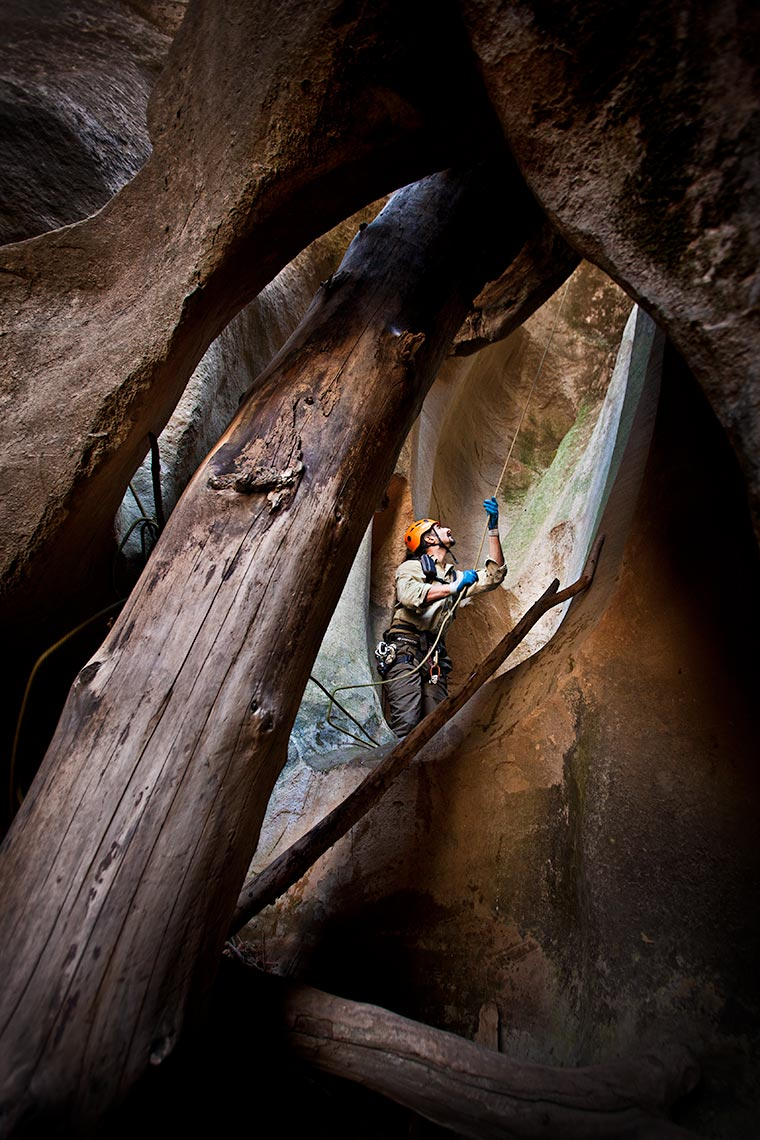 A canyoneer pulls his rope down in a deep canyon filled with debris in Utah
