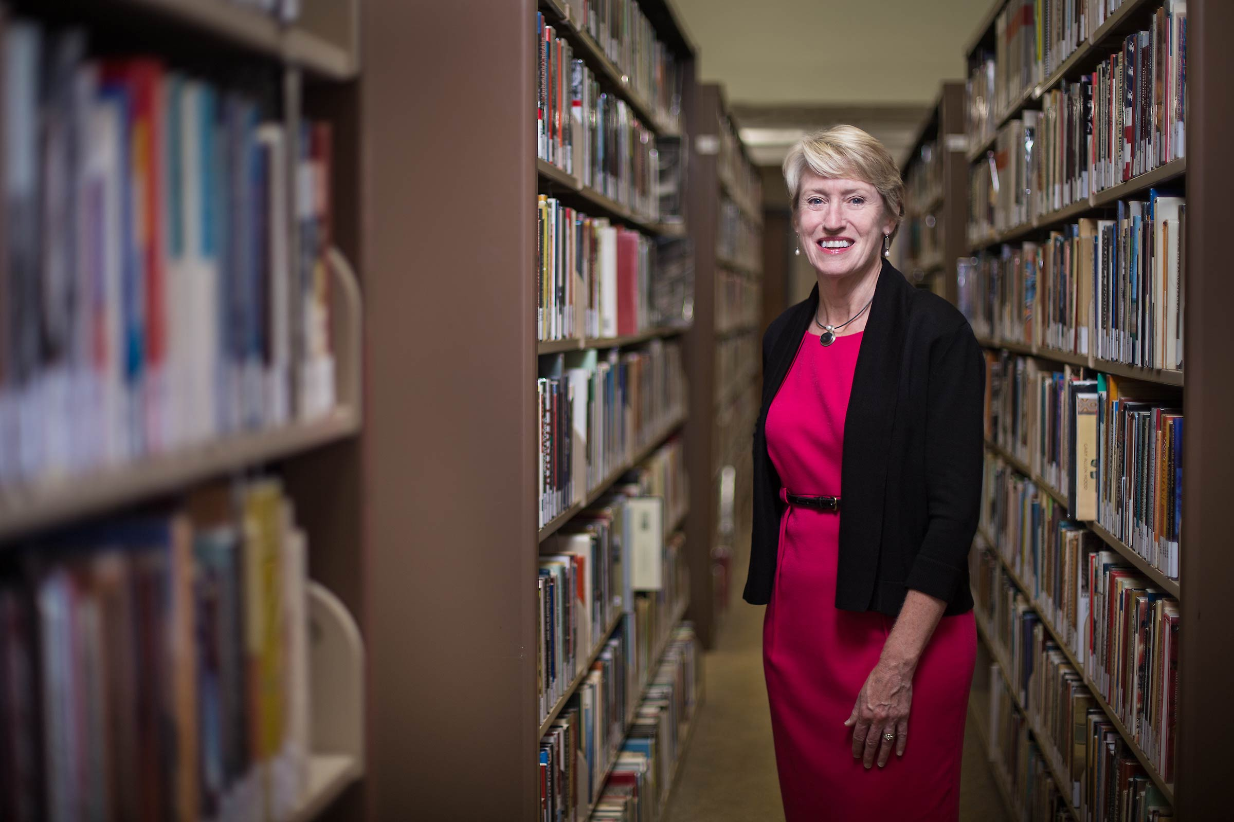 A female  president of a New England College posed on campus amid rows of books