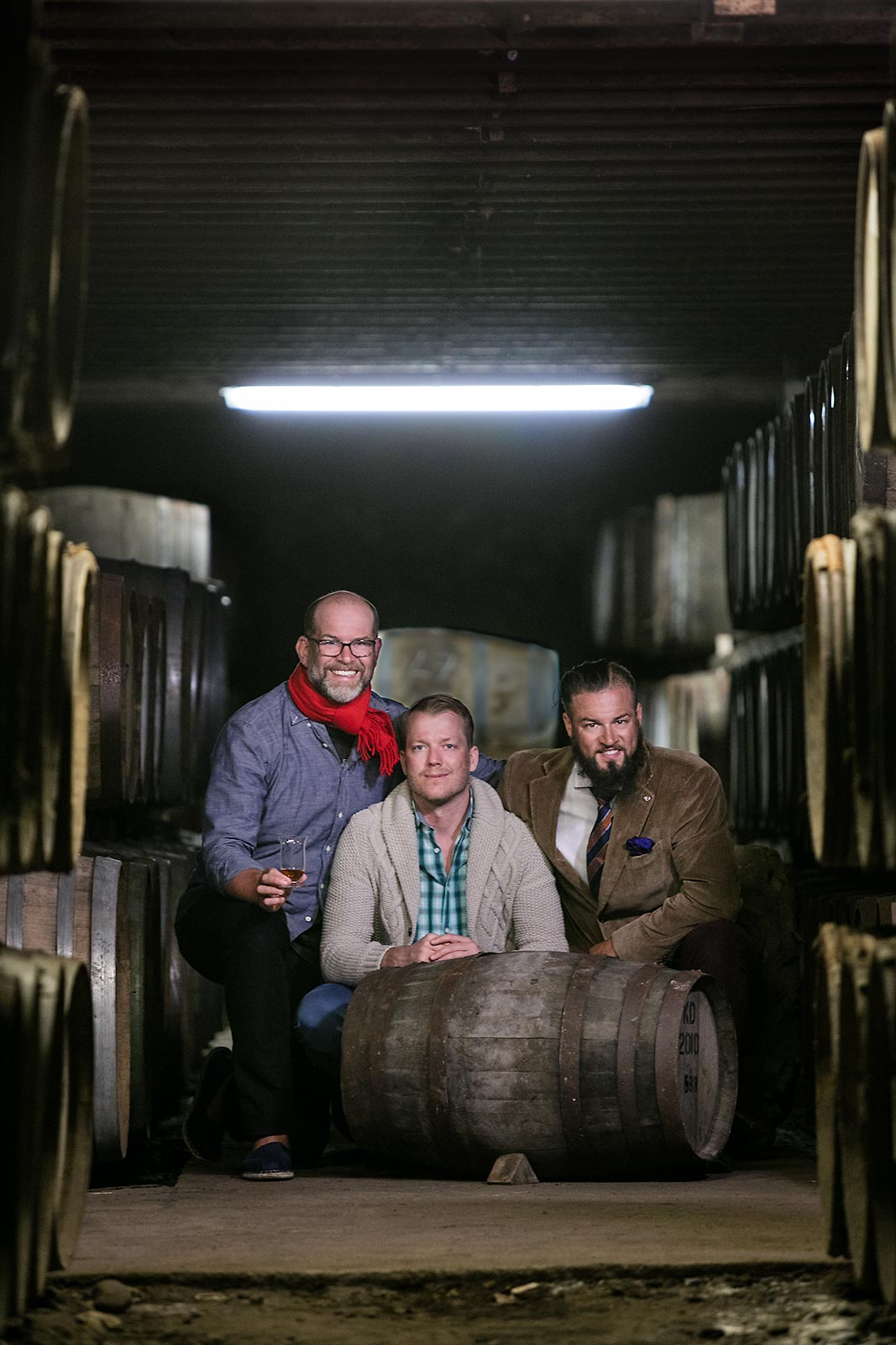 Young entrepreneurs pose near a whiskey barrel at a distillery in Islay Scotland