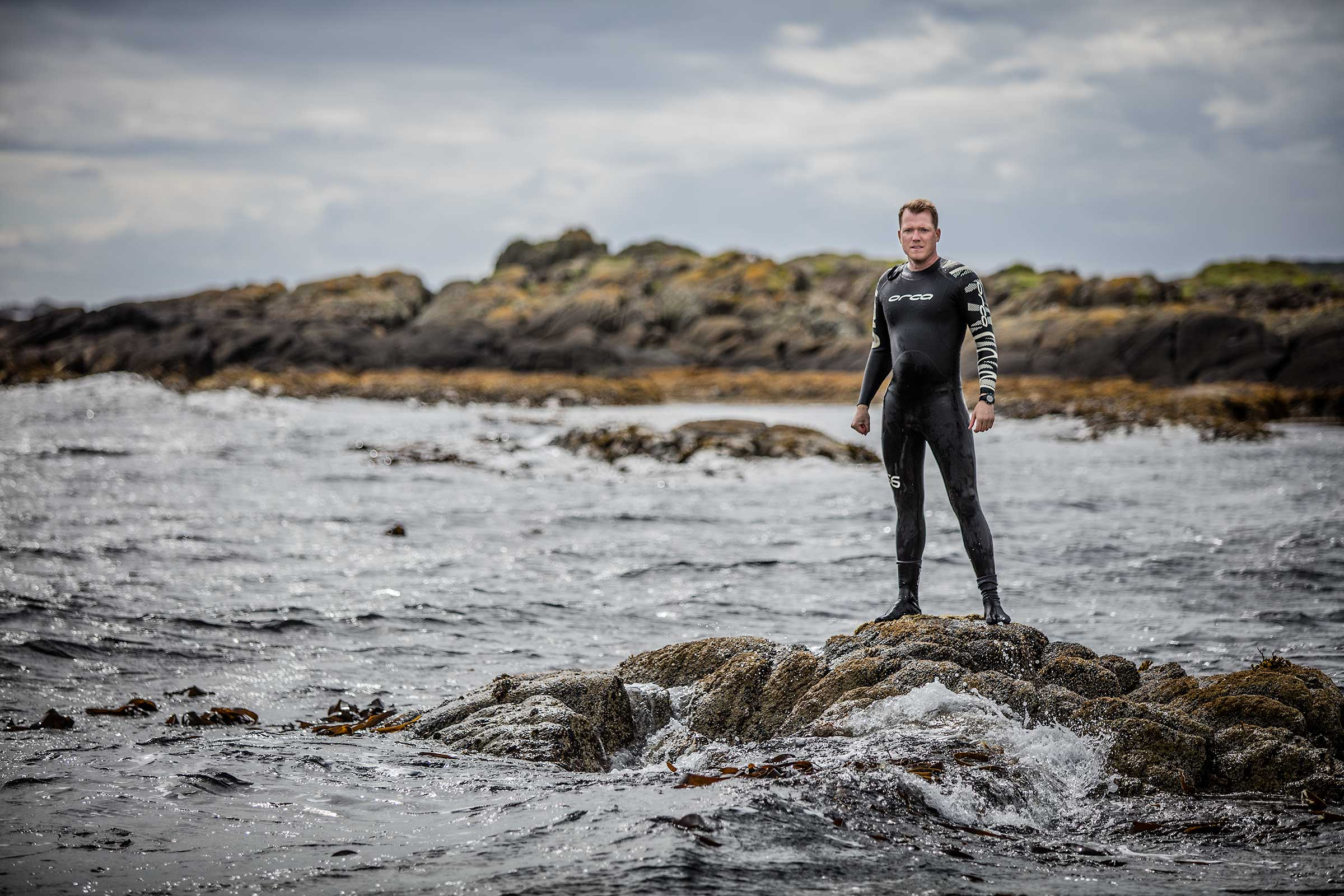 dramatic portrait of long distance open water swimmer on rocks among ocean waves