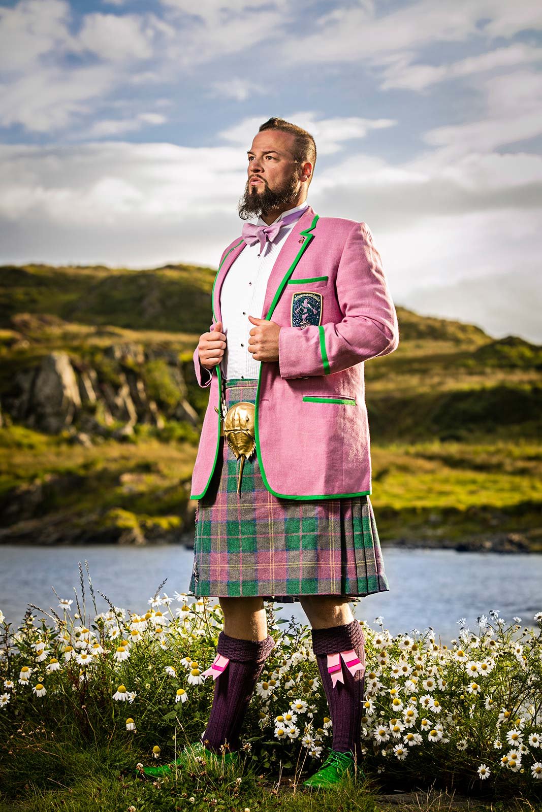 A location portrait of a  man in fashionable kilt amid flowers in Scotland