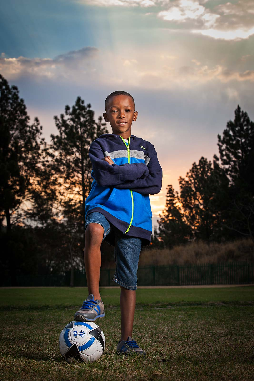 An inspirational young boy with a soccer ball in field at sunset