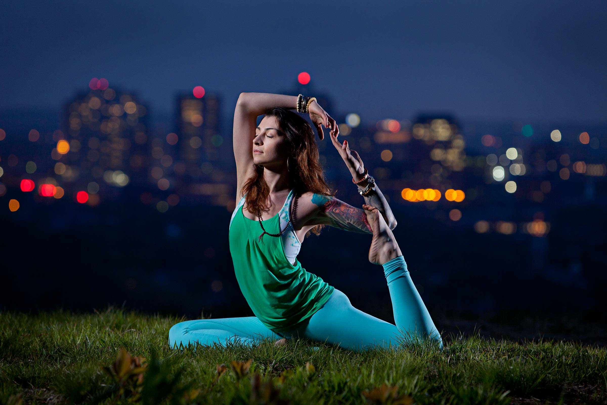 a young women practicing yoga at sunset with city scape in background