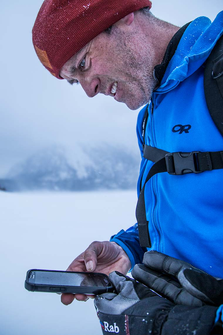 closeup of a man navigating with GPS in remote winter location during storm