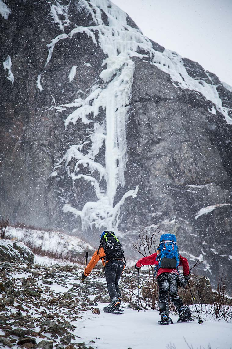 A pair of ice climbers ascends a steep hill with snowshoes during storm in Newfoundland