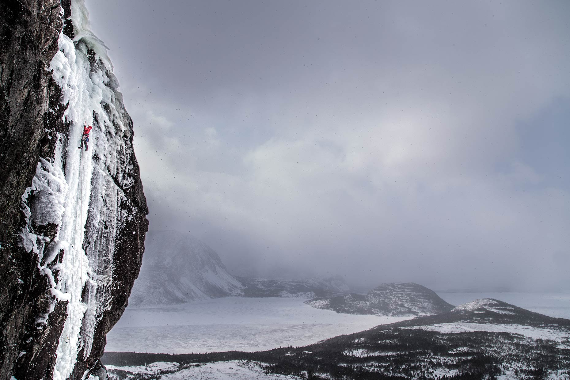 A dramatic panoramic landscape of an ice climber ascending a fjord in Newofoundland