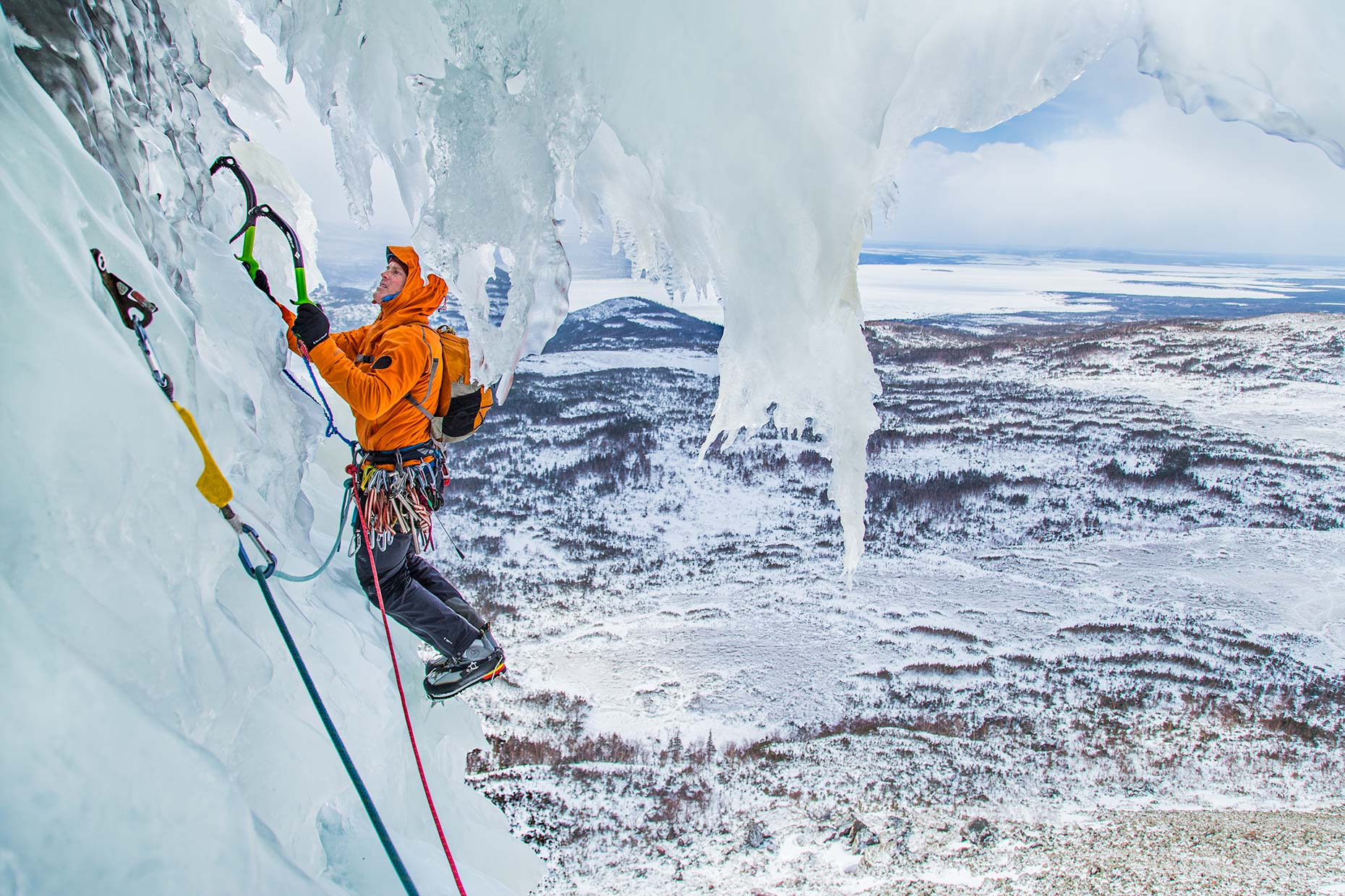 An ice climber navigates a bizarre windswept curtain of ice perched over a Newfoundland fjord