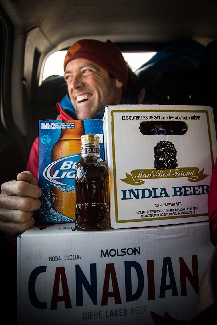 Closeup of an iceclimber laughing while packed into the car with a large pile of beer