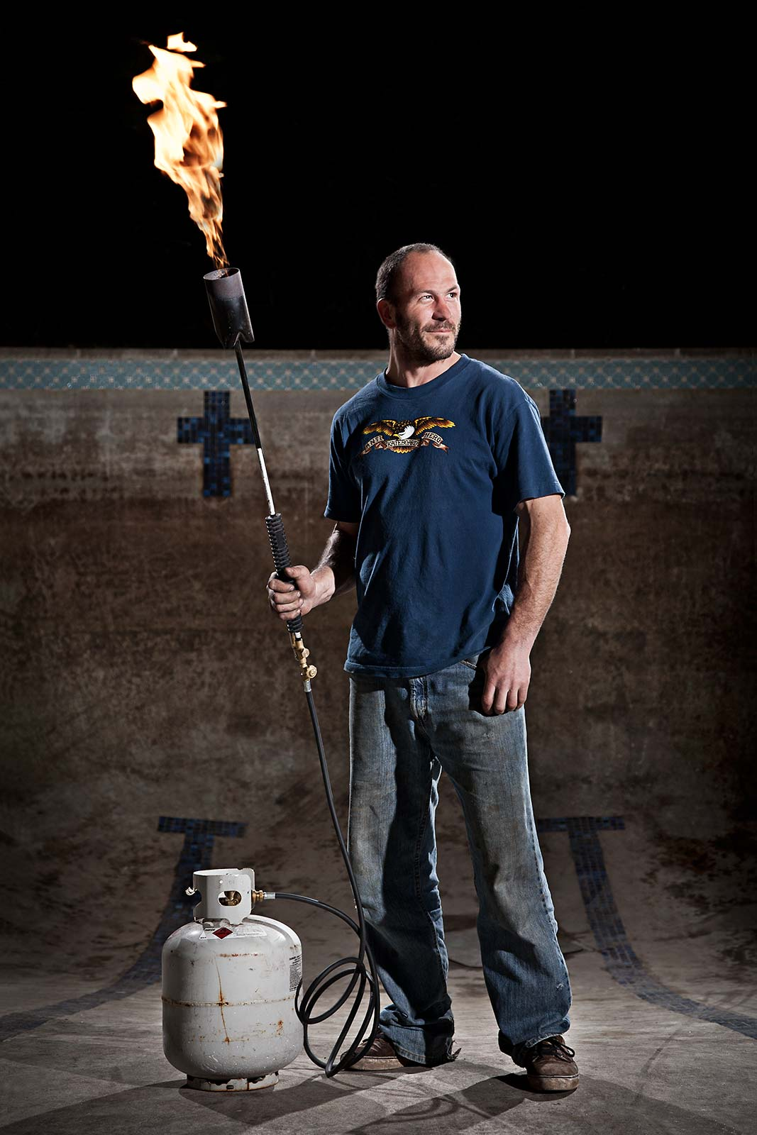 Portrait of a man wielding a torch in an empty swimming pool in Connecticut