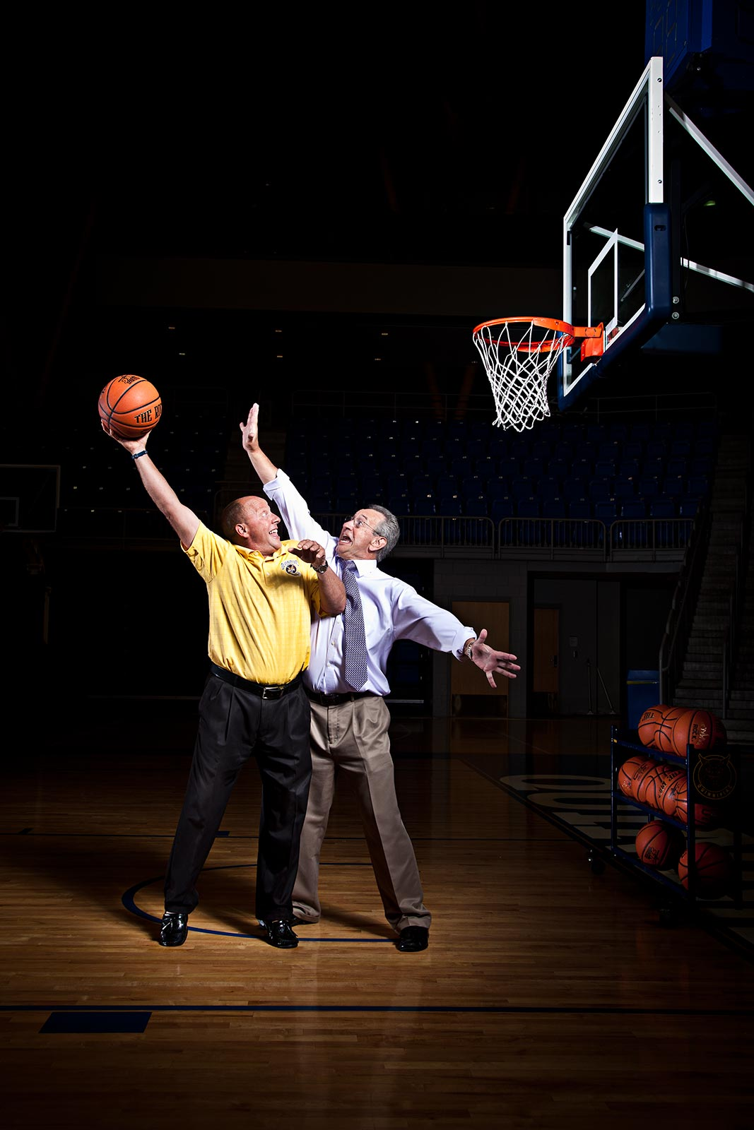 dramatic scene of two sports announcers playing basketball wearing suits in areana