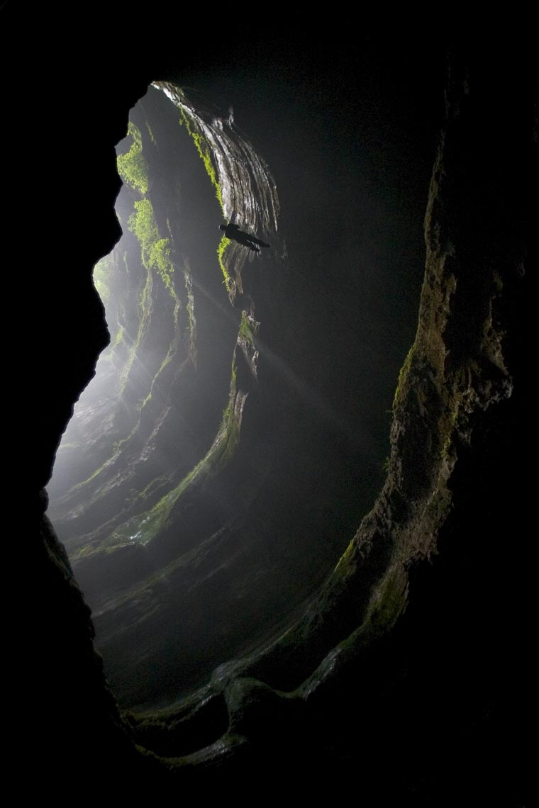 Dramatic view of an adventurer rappeling into a deep dark cave opeing