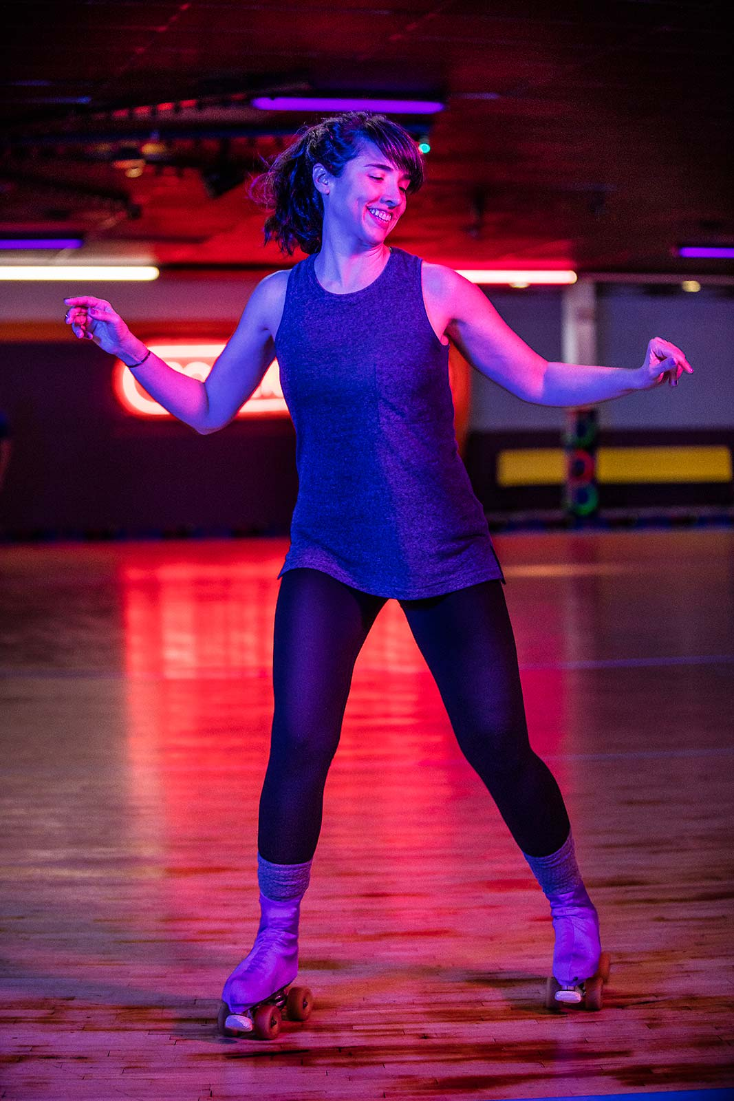 A vibrant colorful portrait of a young woman dancing on roller skates at a rink in Connecticut