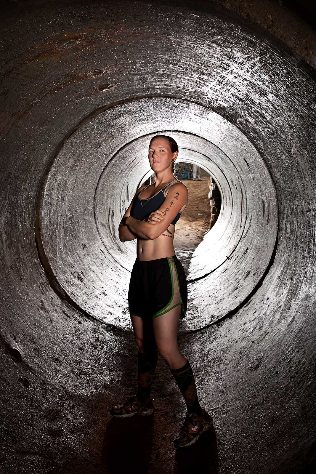 A fit athletic young woman poses in a tube during an adventure race in Connecticut