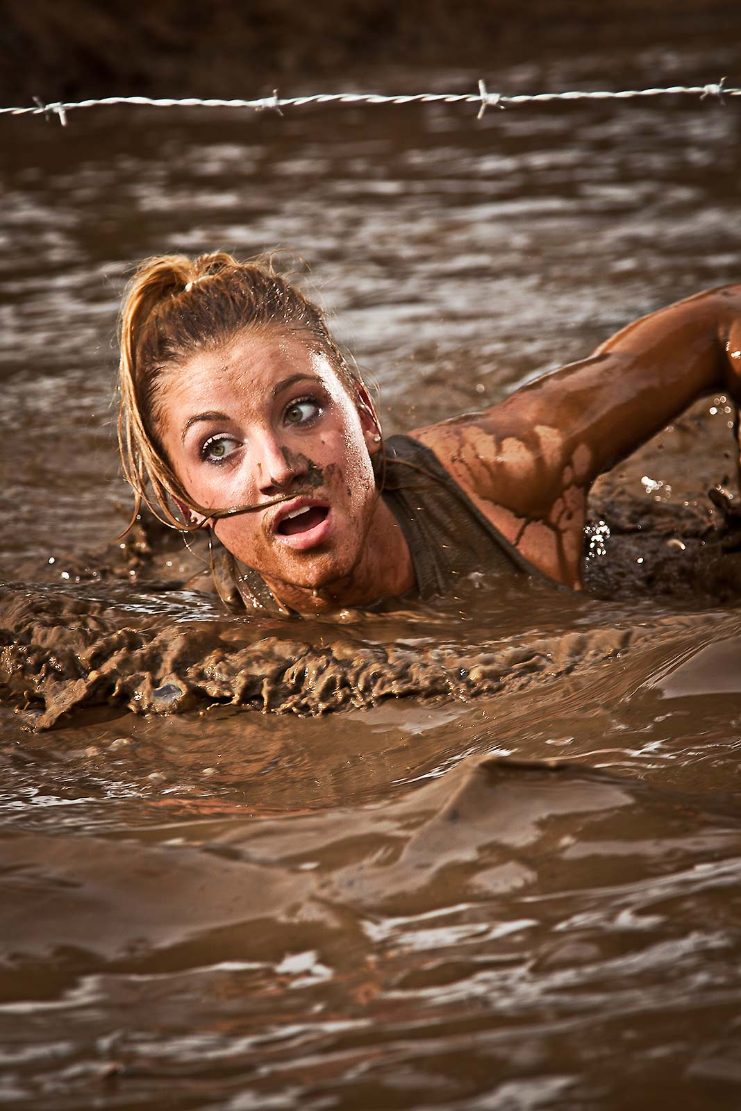 A fit athletic young woman swimming thru a mud obstacle as part of an adventure race in Connecticut