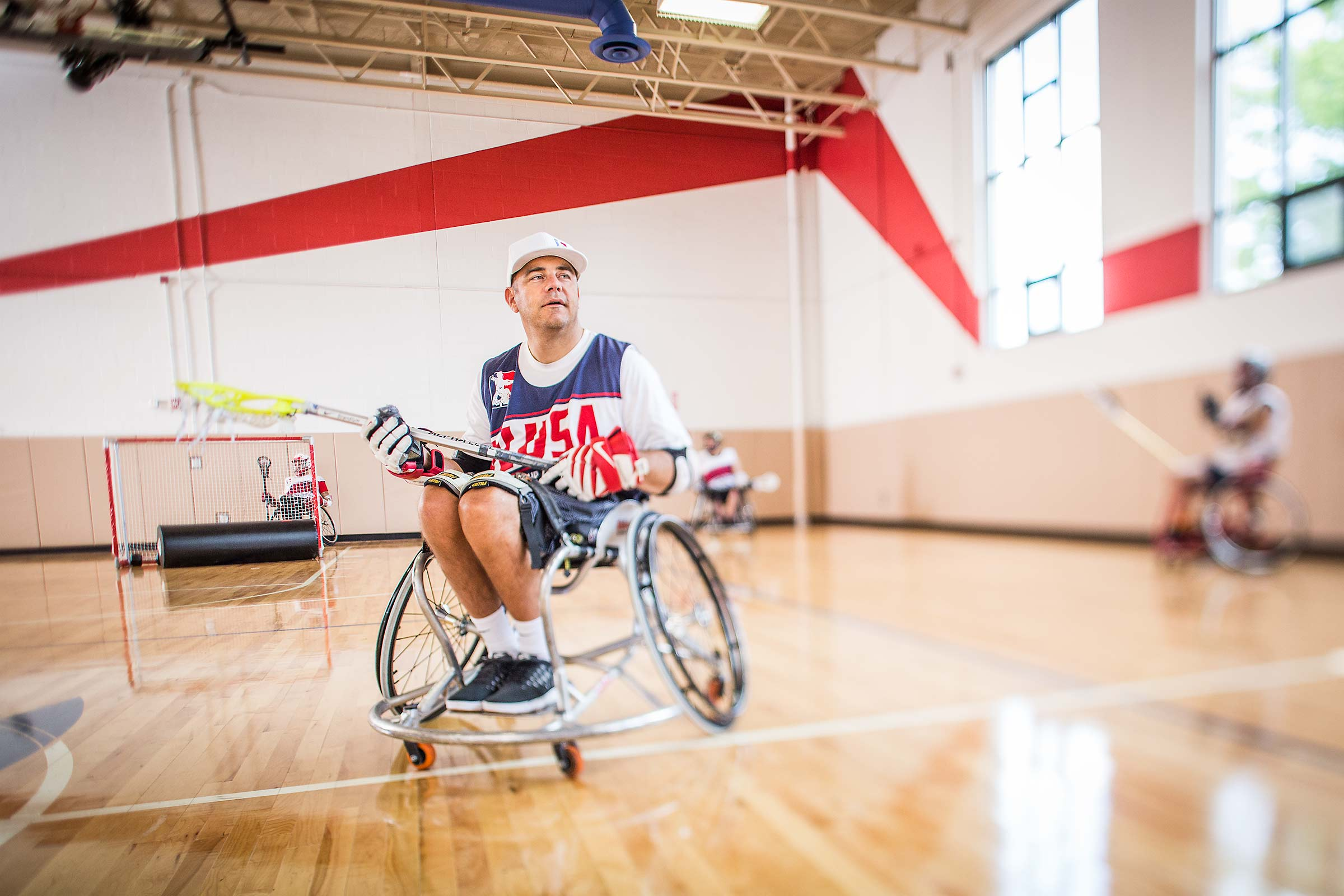 Wheelchair lacrosse founder throwing ball on an indoor court in Connecticut