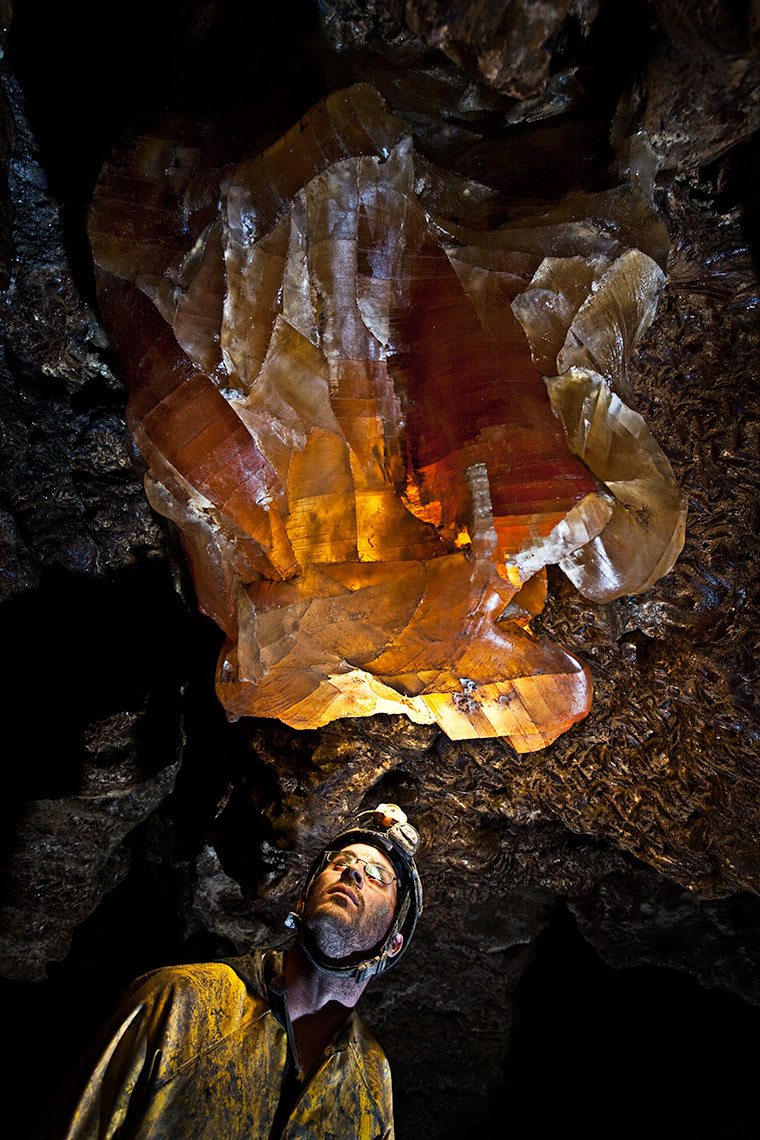 A caver inspects a glowing giant gypsum crystal in a labyrinth cave system in Ukraine