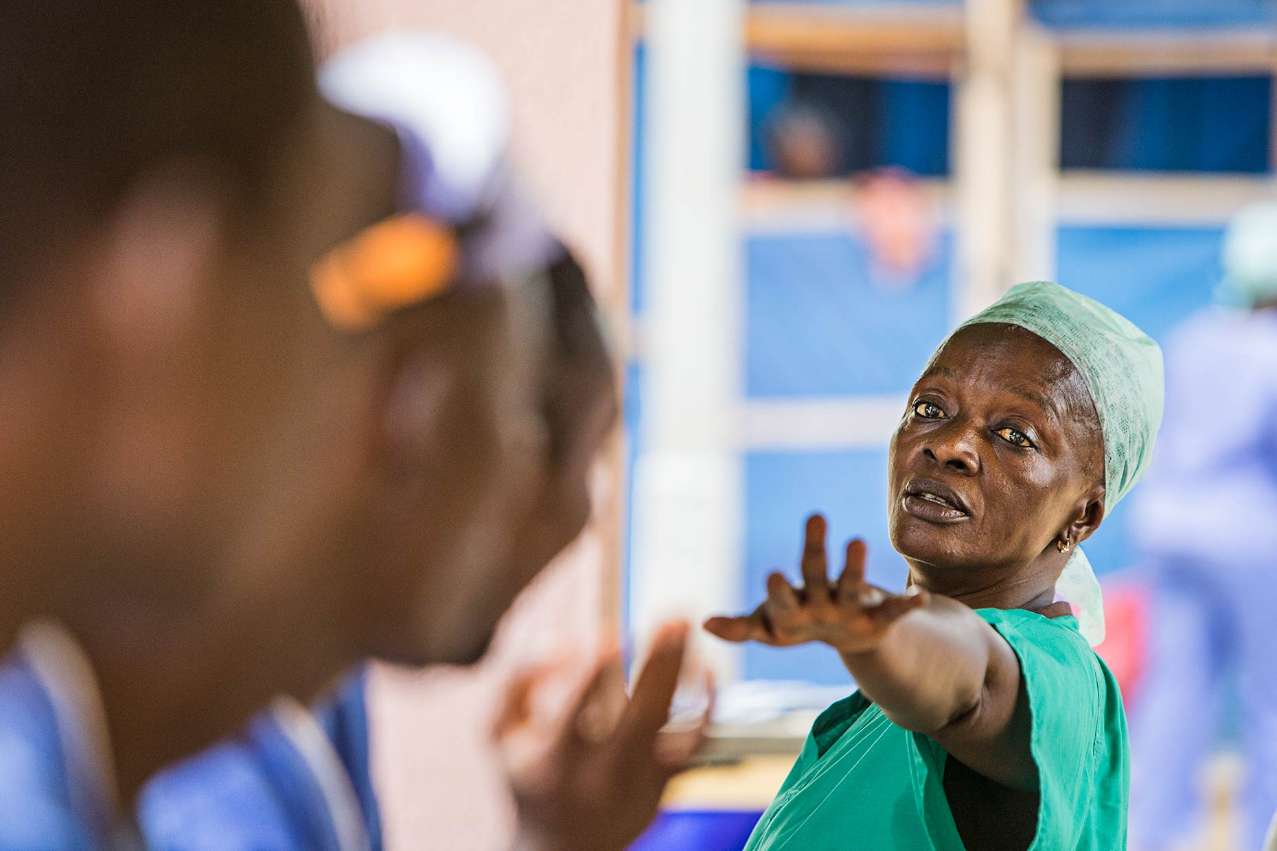 A lead nurse passionately commanding her staff at a meeting in a West African Ebola center