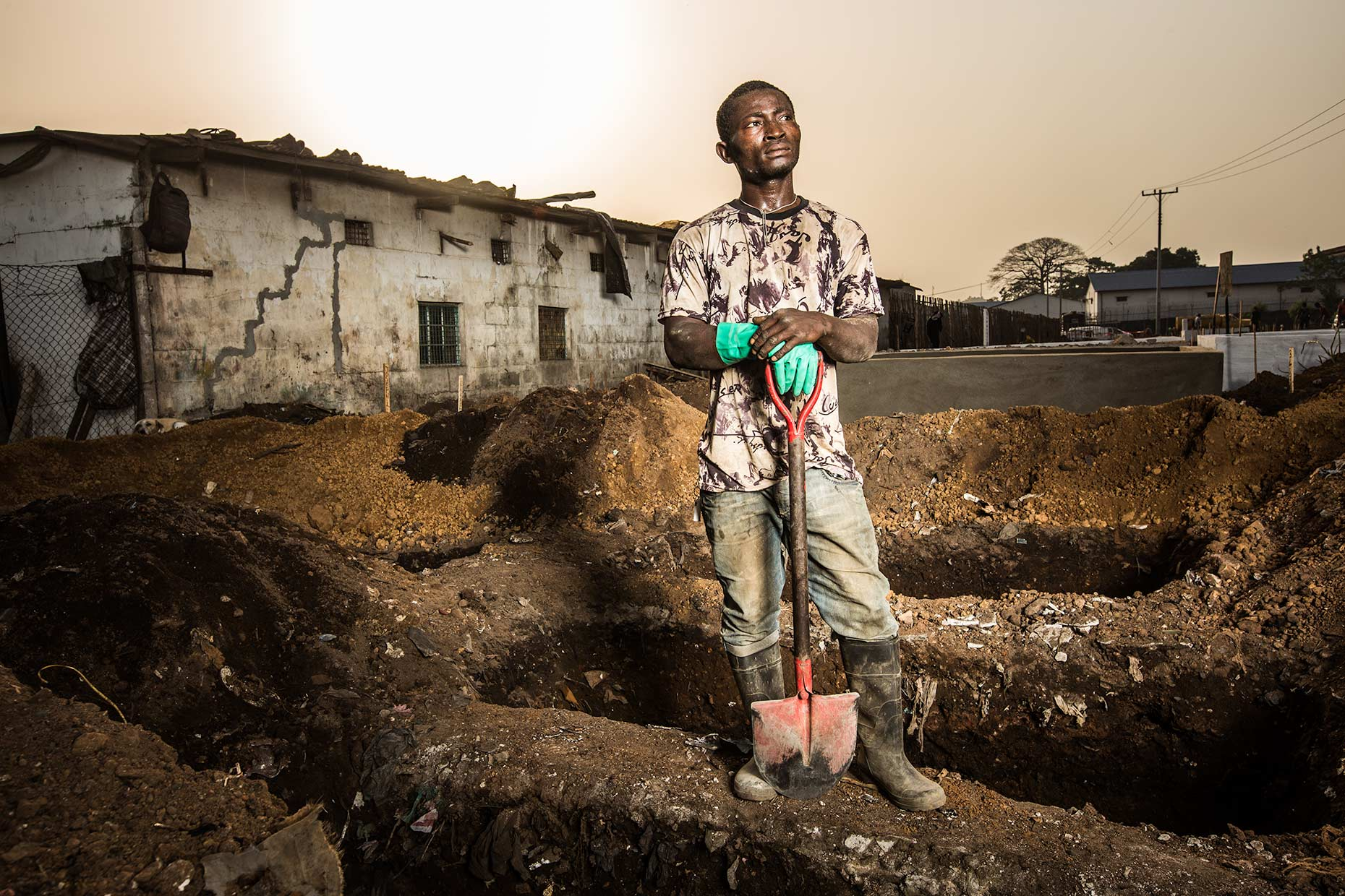 A worker stands next to a row of open graves awaiting Ebola Victims