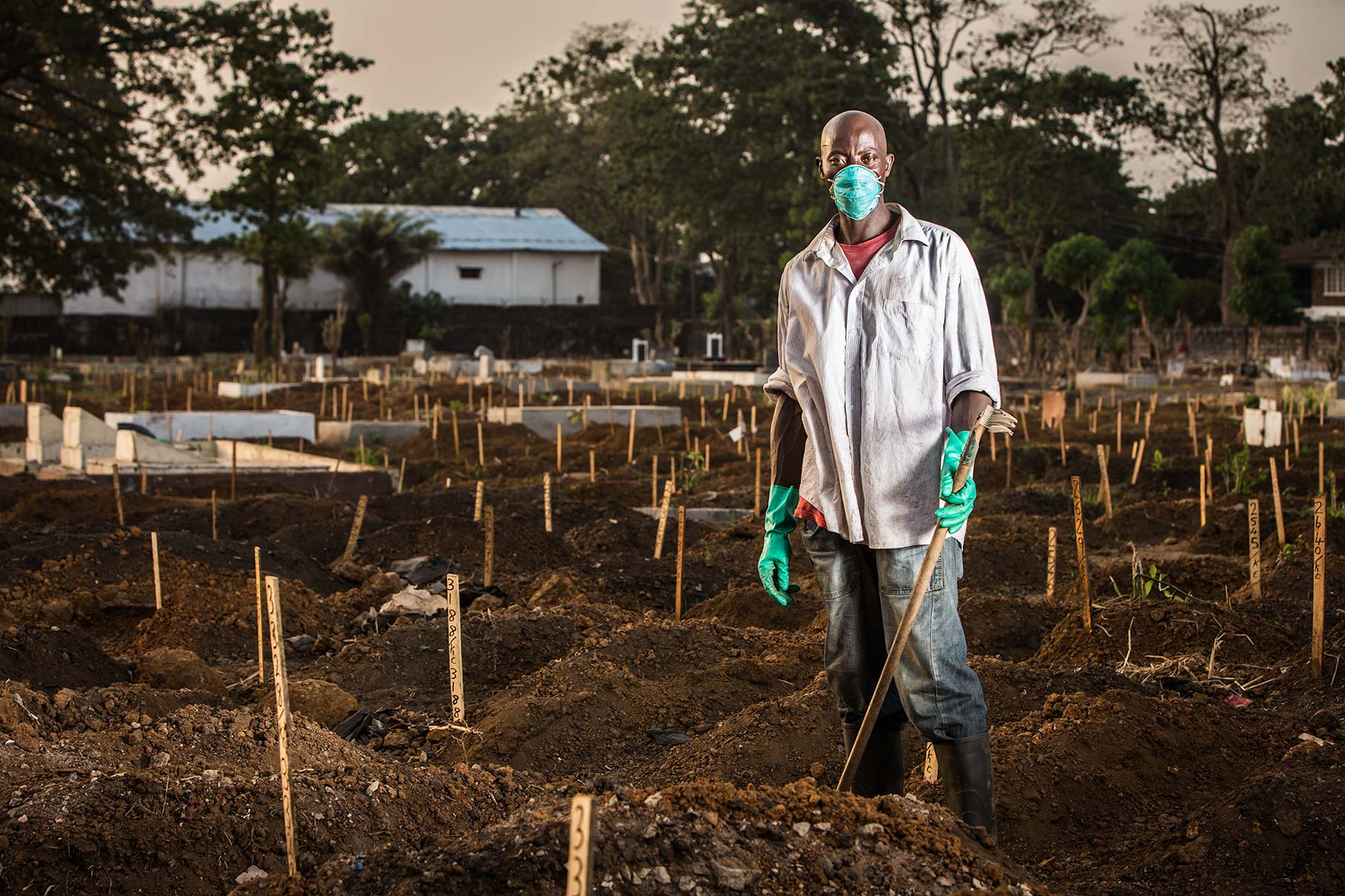 A worker wearing surgical mask and gloves while digging in a smokey Ebola graveyard