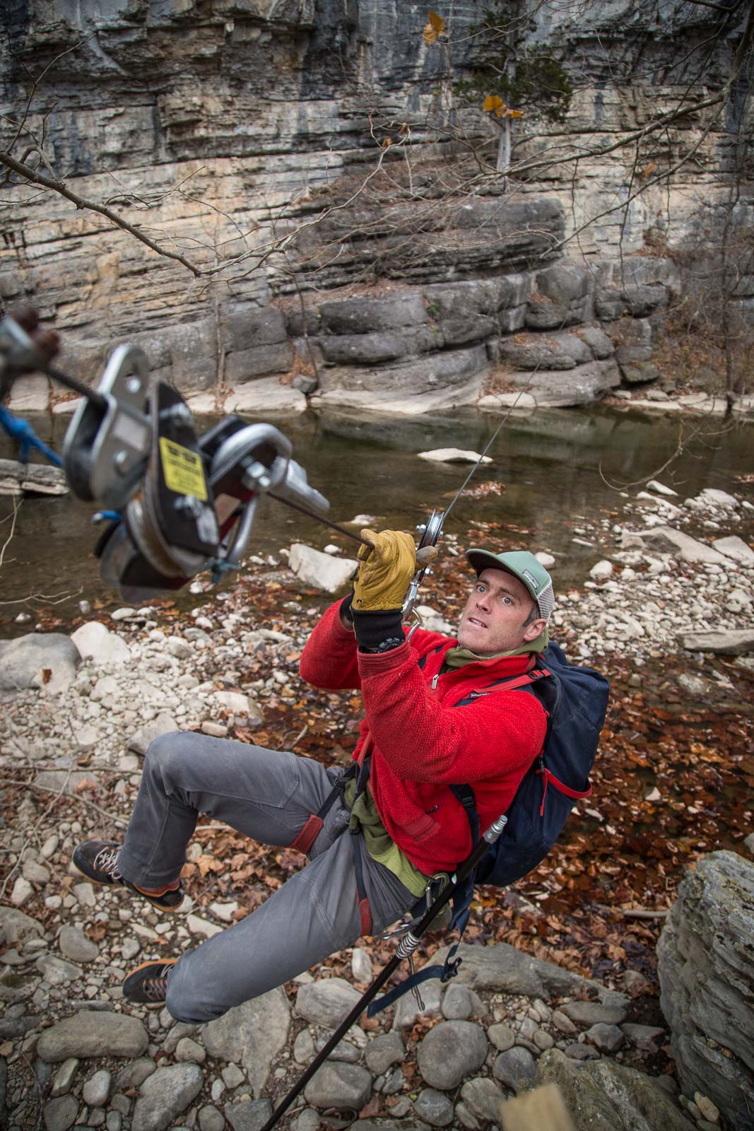 An adventure athlete pulls himself on a cable pulley above a swift river