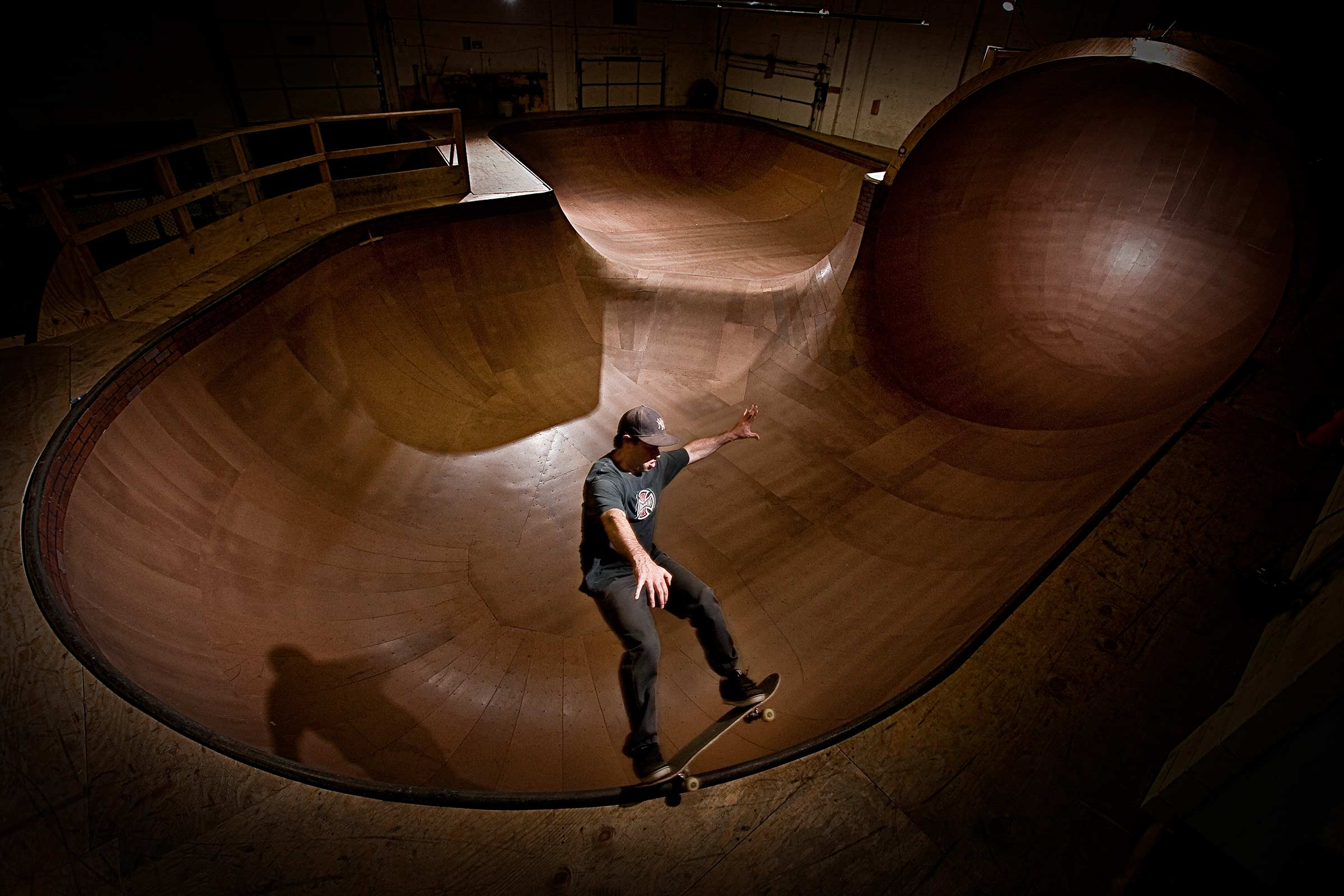 A dramatically lit action shot of a man skateboarding at an indoor park in Connecticut