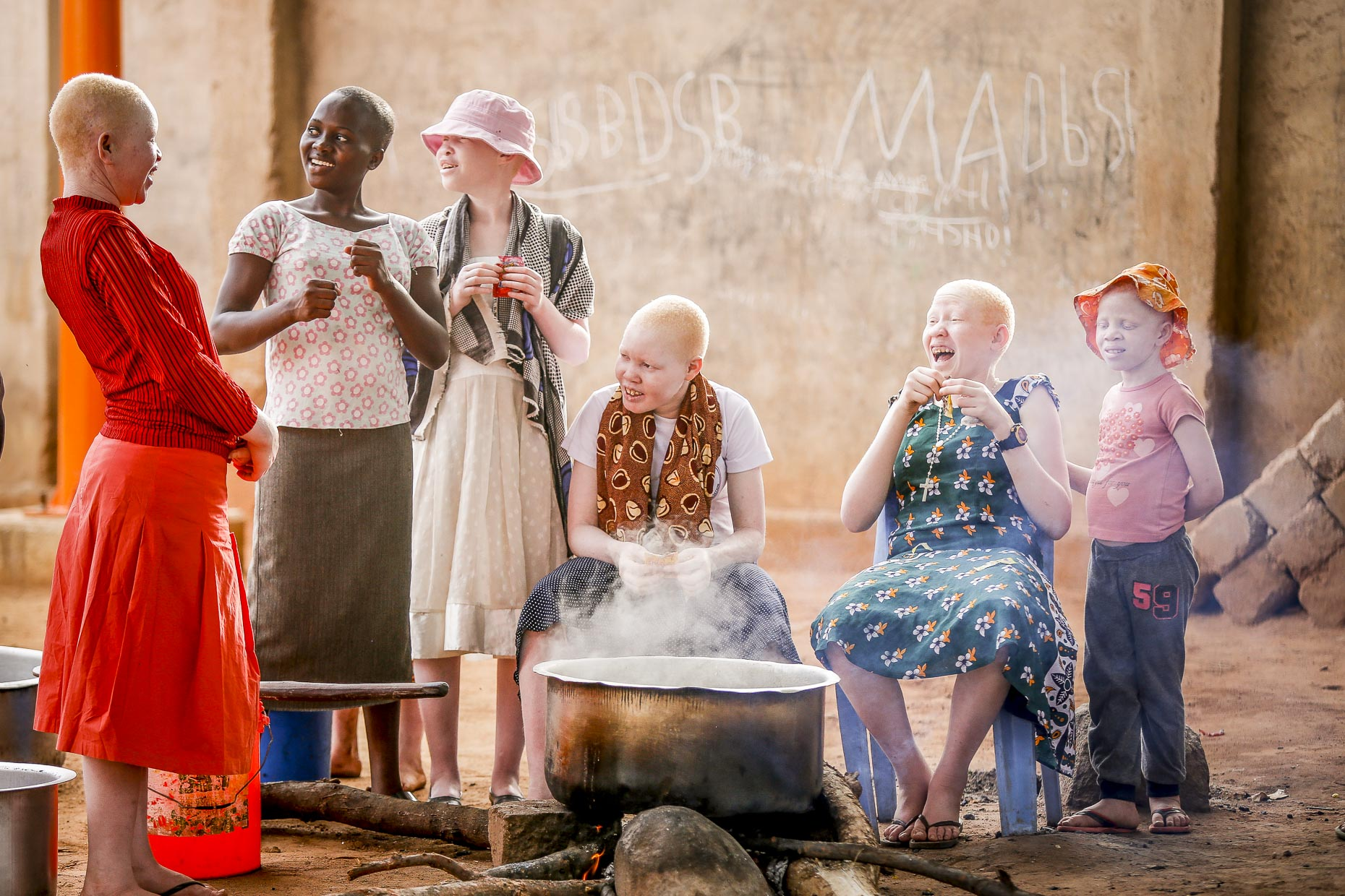 A group of childern laughing together gathered around an outdoor kitchen in an orphanage in East Africa