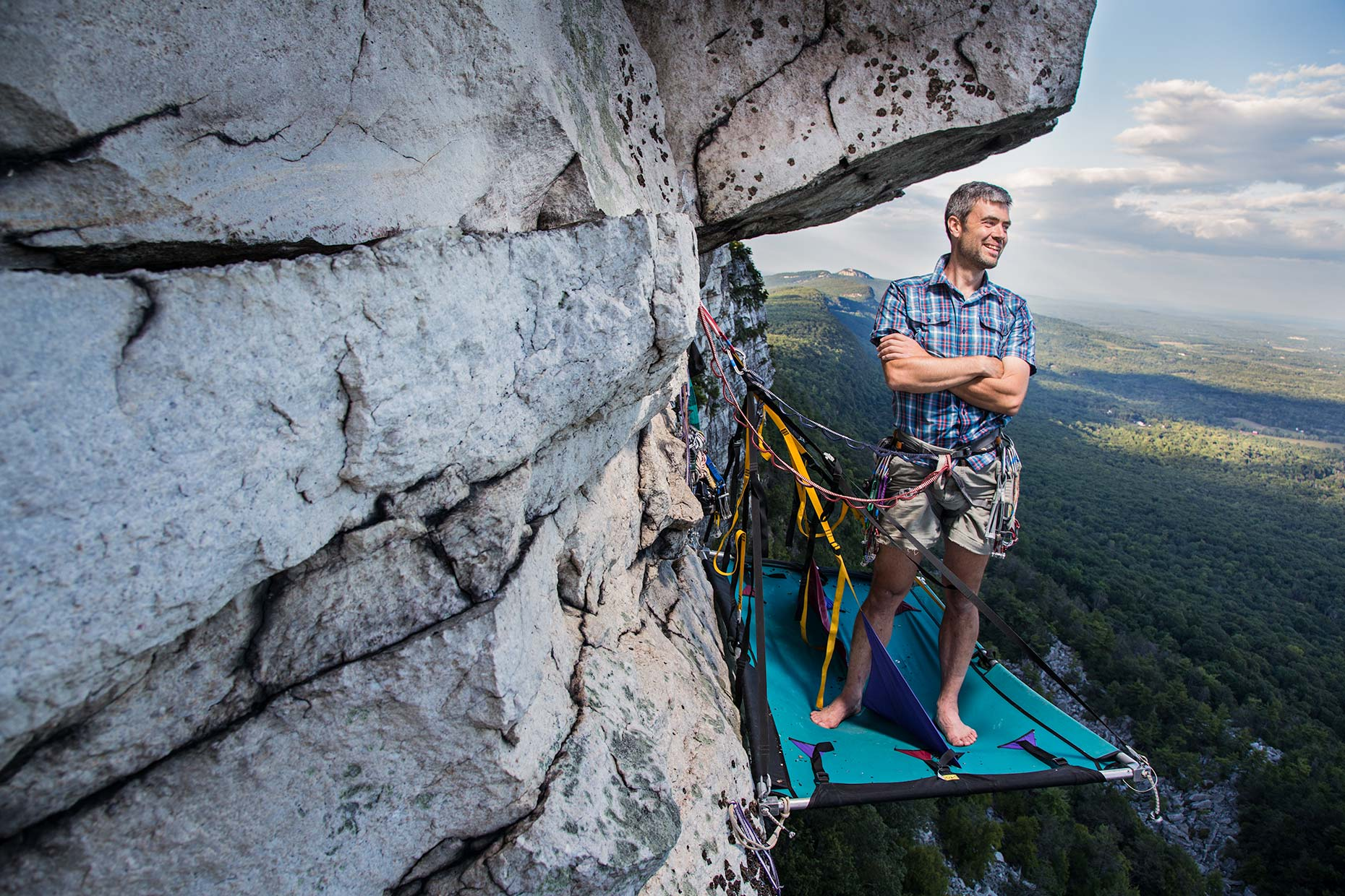 A confident portrait of a rock climber standing on a hanging ledge on a cliff in New york
