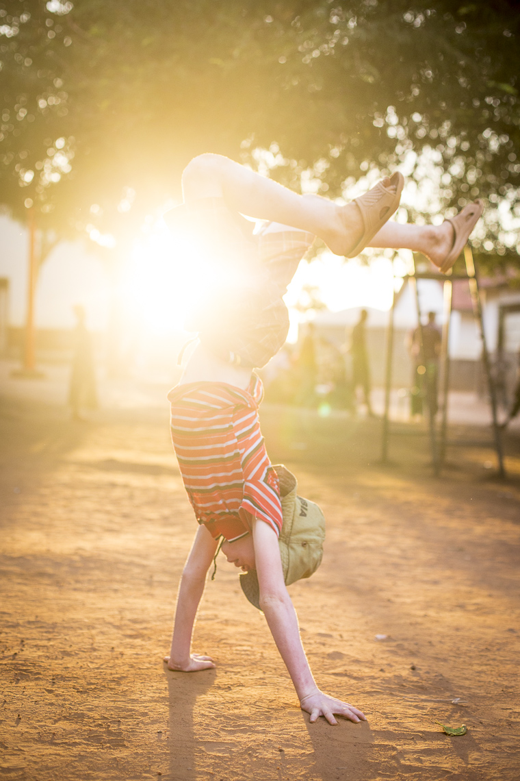A young boy playful does a handstand in the setting sun in an East African school for Albino Children