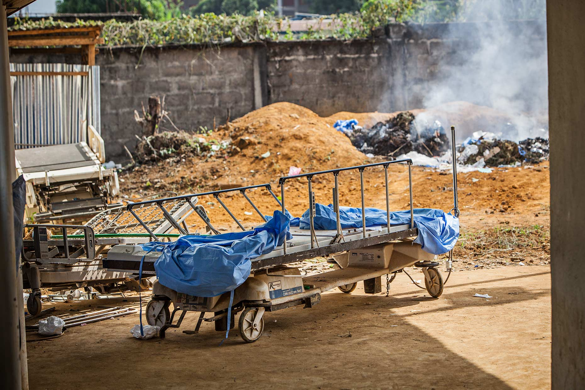 An empty gurney sits in front of a burning pile of medical waste at an Ebola hospital