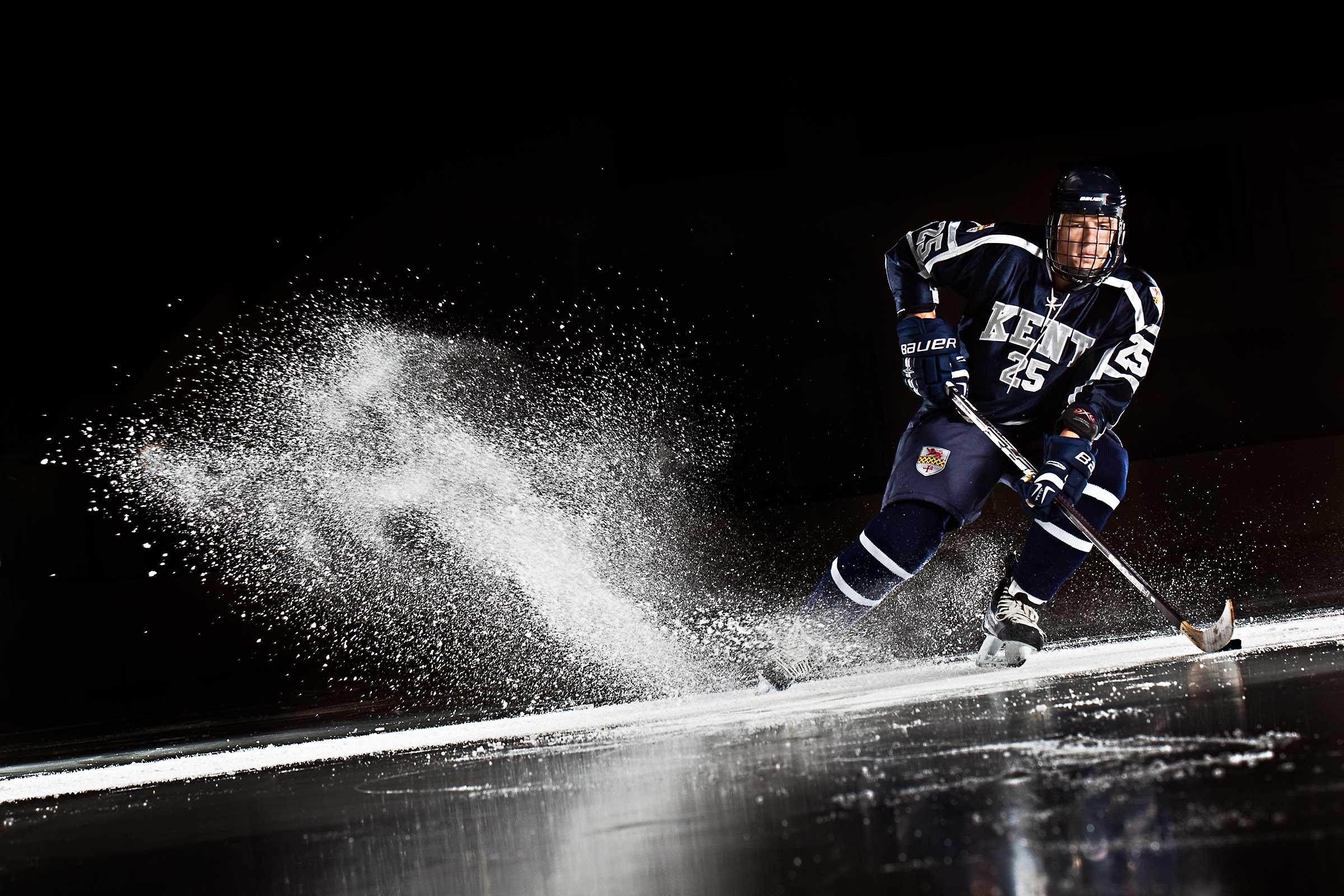 Dramatically lit action shot of Hockey player kicking up a wave of ice in Hockey arena